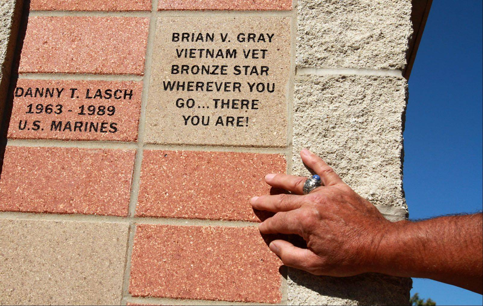 Bill Starr, a retired Army lieutenant colonel, reads a brick on the new veterans memorial. Starr, who served in Vietnam, Bosnia and Kosovo has a brick with his name on it, and is one of several speakers on Saturday.