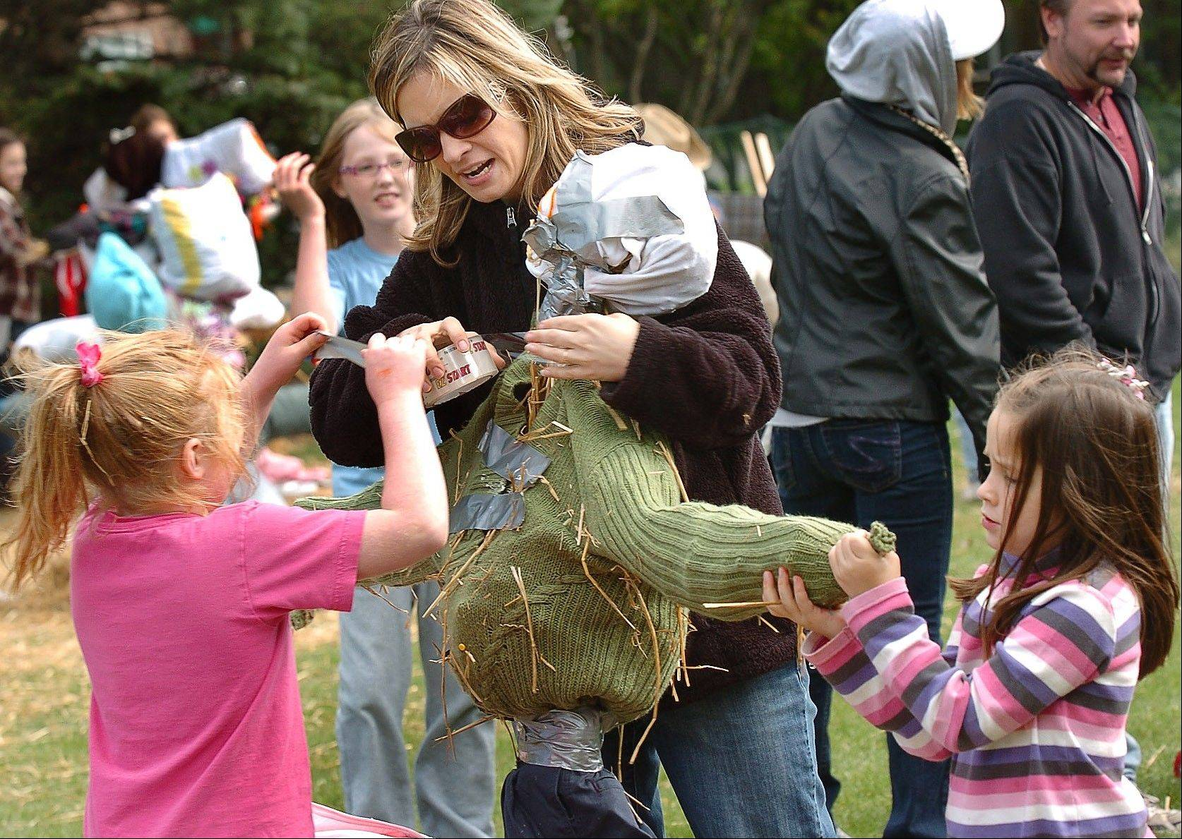 In a photo from 2010, Erin Trunda, middle, works on a scarecrow for the scarecrow competition with Rebecca Caliendo, left, and Katie Trunda.