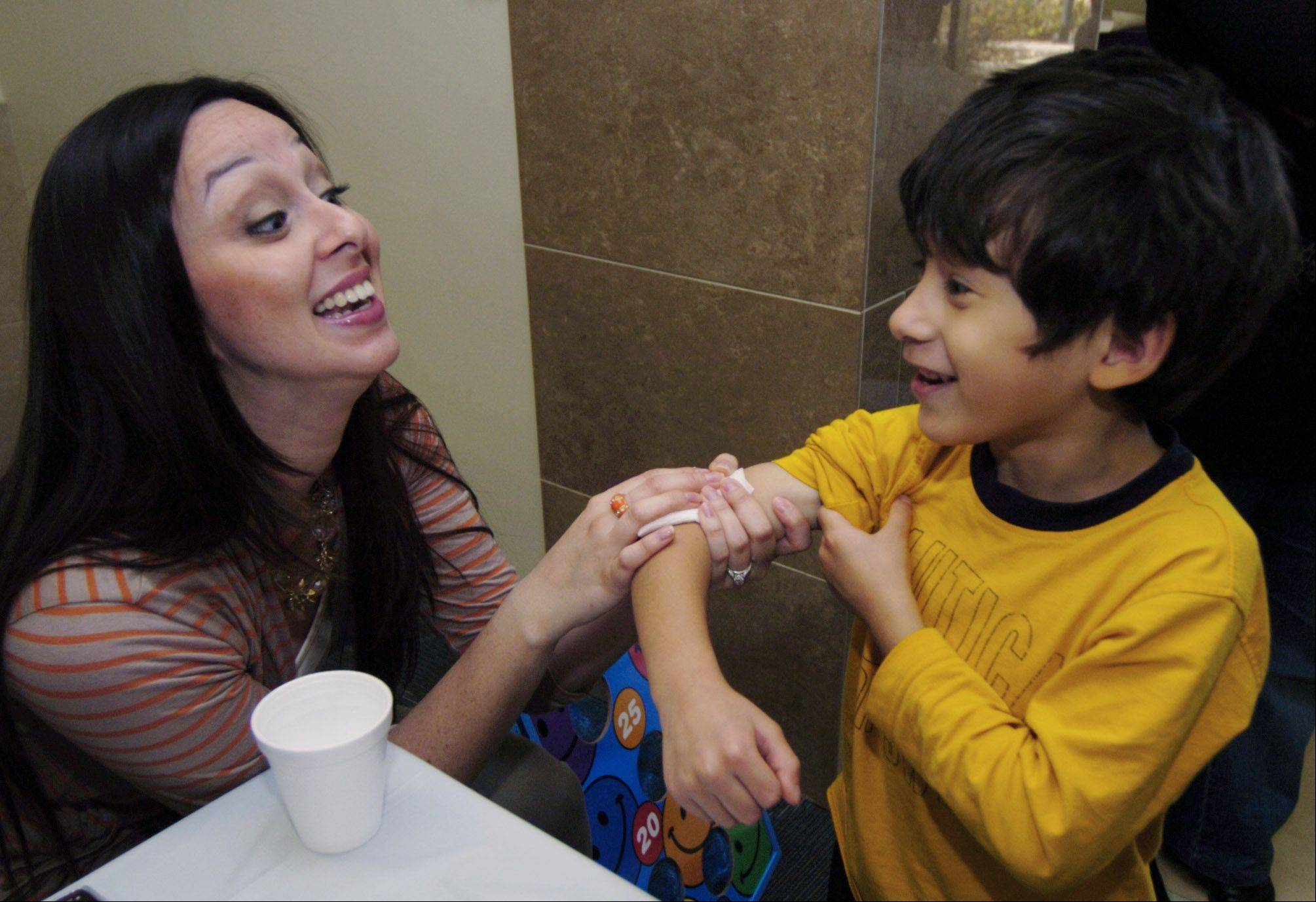 Patty Anderson, a counselor with Health and Human Services, counts to 20 with Ricardo Hernandez, 5, of Hoffman Estates as Anderson applies a temporary tattoo Ricardo won at the 2011 fiesta.