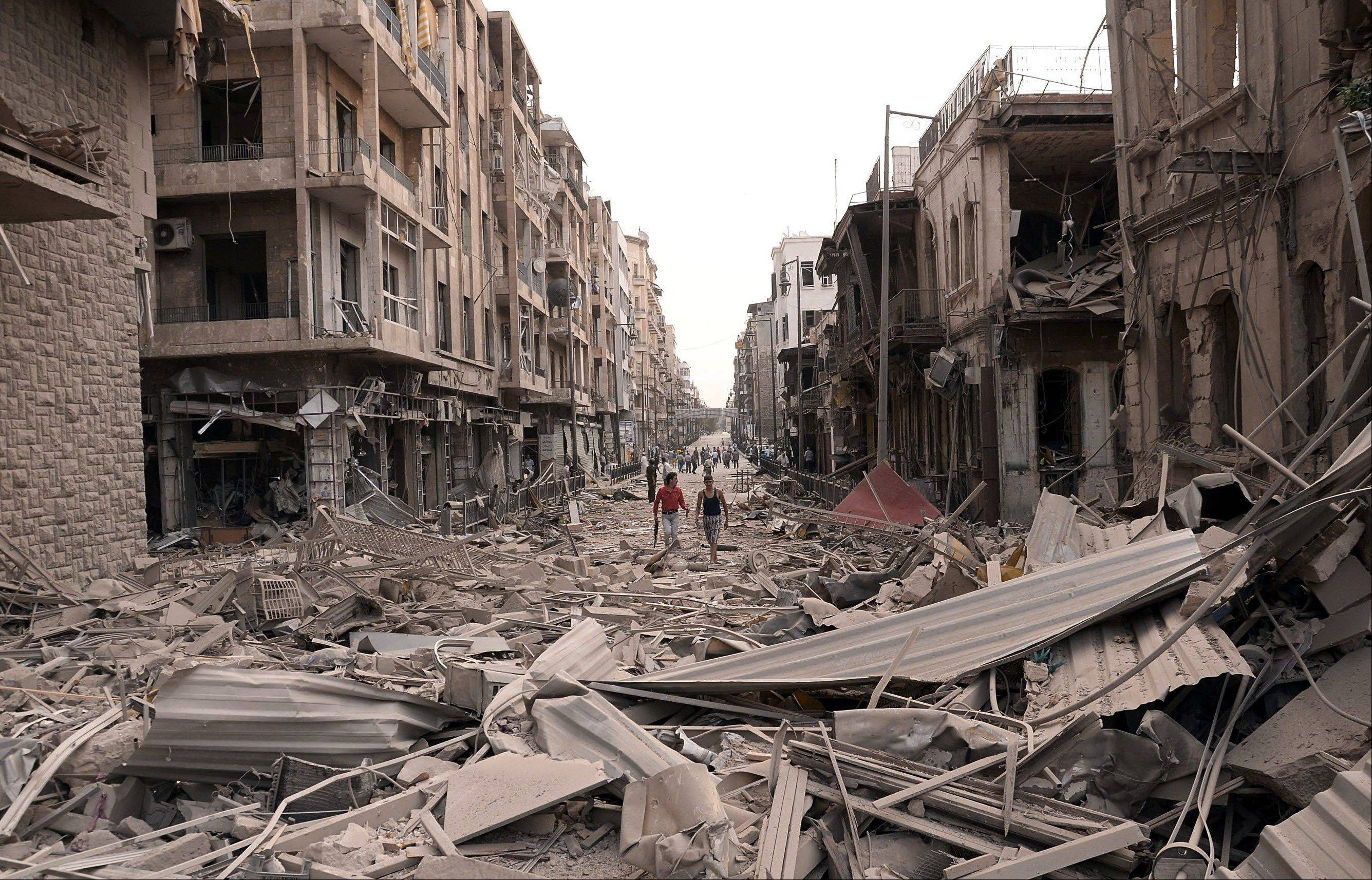 Syrian men walk at a street between destroyed buildings where triple bombs rocked at the Saadallah al-Jabri square, in Aleppo city, Syria, Wednesday.