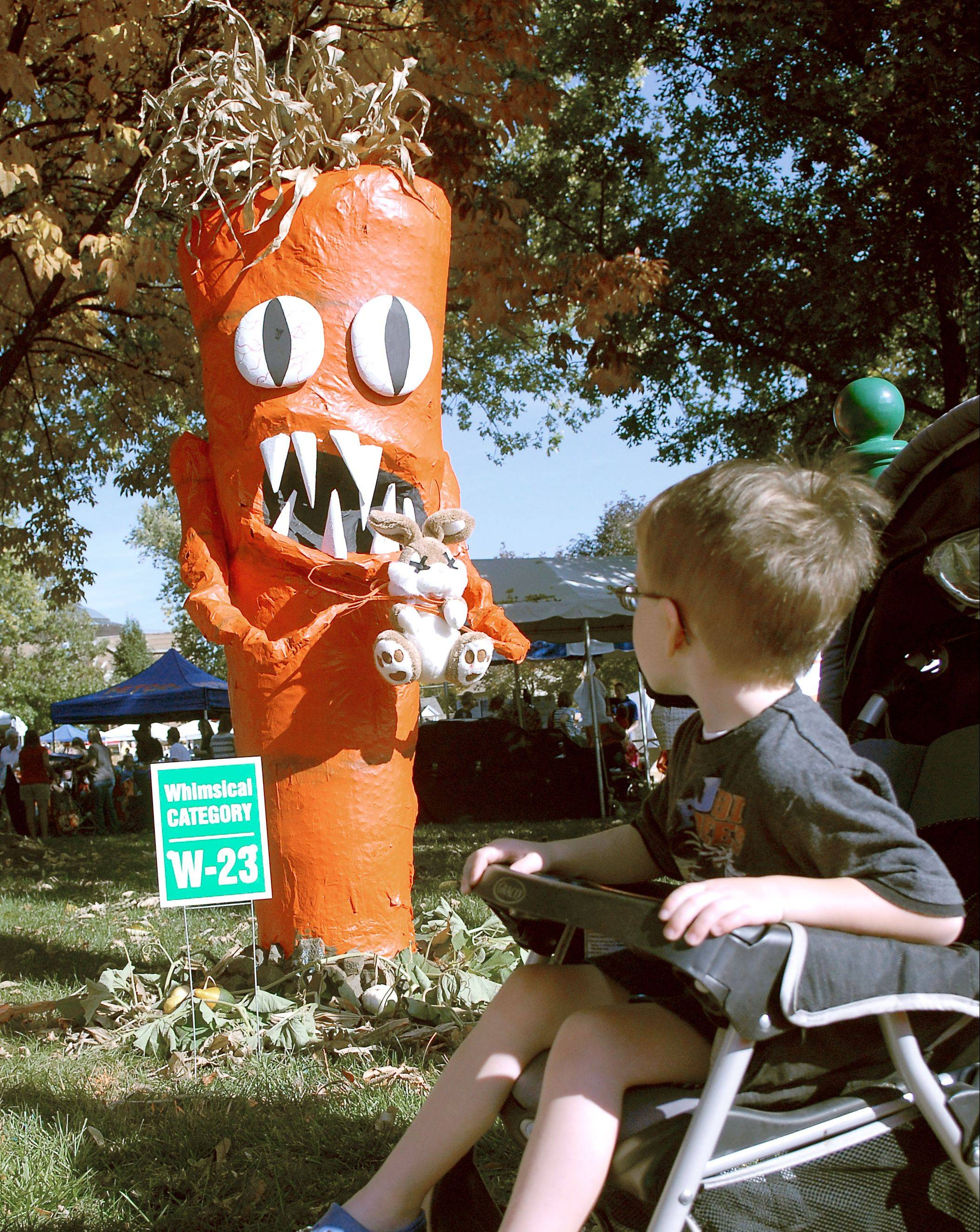 Spencer McCall, 4, of Campton Hills has a great seat while viewing entries in the whimsical category at the St. Charles Scarecrow Fest in Lincoln Park last year.