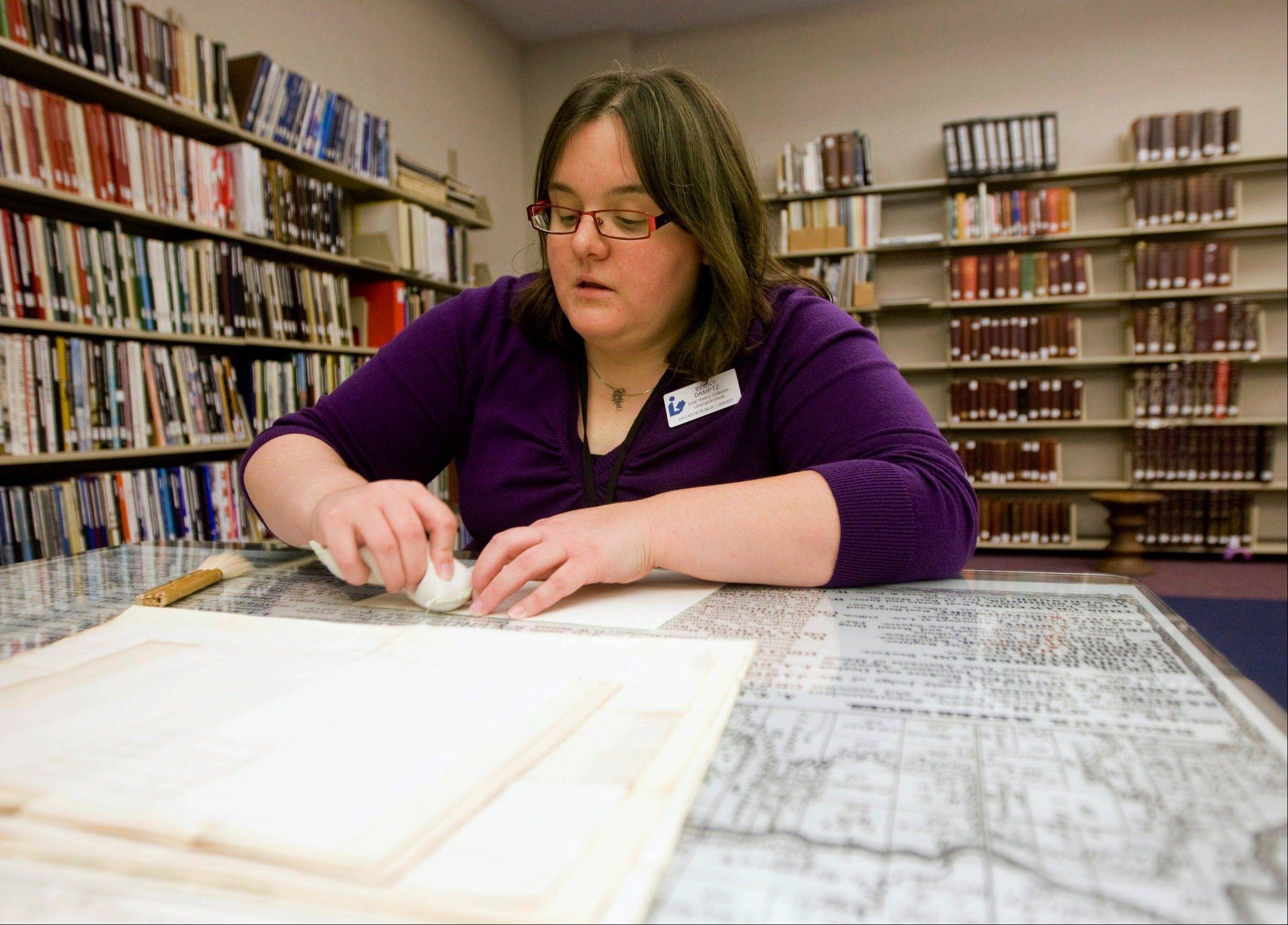 Rebecca Damptz, local history librarian/archivist at the Decatur Public Library, cleans an old document in Decatur.