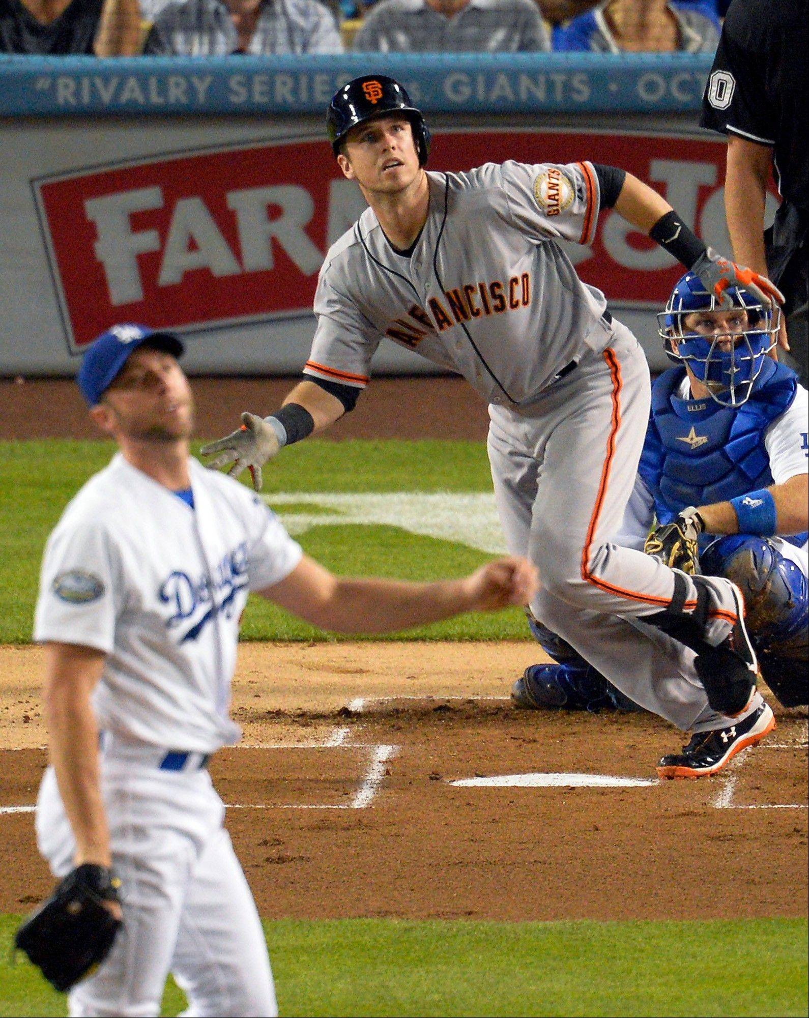 The Giants� Buster Posey watches his solo home run off Dodgers starting pitcher Chris Capuano on Tuesday in Los Angeles.