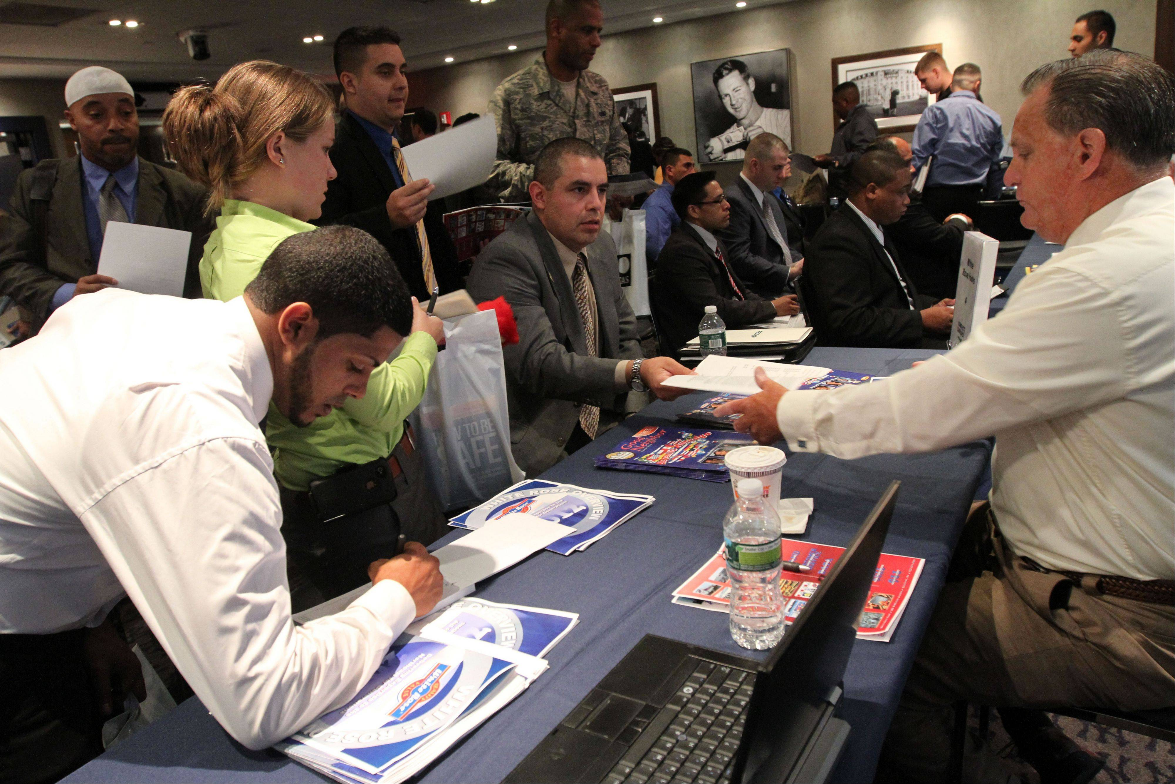 In this Sept. 28 photo, Veteran Luis Gomez, 40, from Dover, N.J., seated center, hands his resume to a representative from White Rose Foods, right, during a job fair at Yankee Stadium in the Bronx borough of New York. A private survey released Wednesday, shows that U.S. businesses hired fewer workers in September than August, a sign that slow growth may be holding back hiring. Payroll processor ADP said Wednesday that companies added 162,000 jobs last month. That's below August's total of 189,000, which was revised lower.