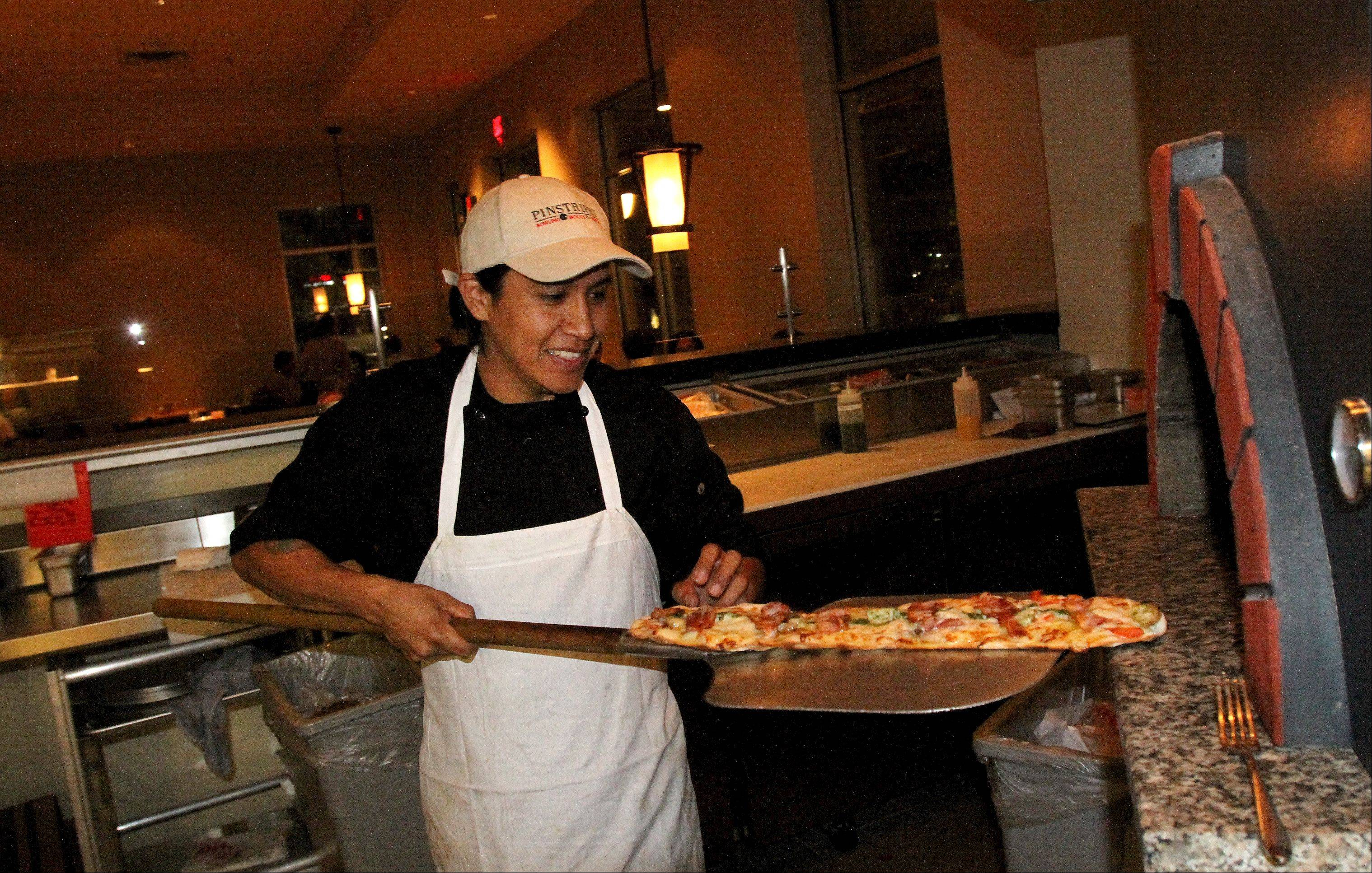 Alberto Salgabo takes a pizza out of the wood-burning oven at Pinstripes.