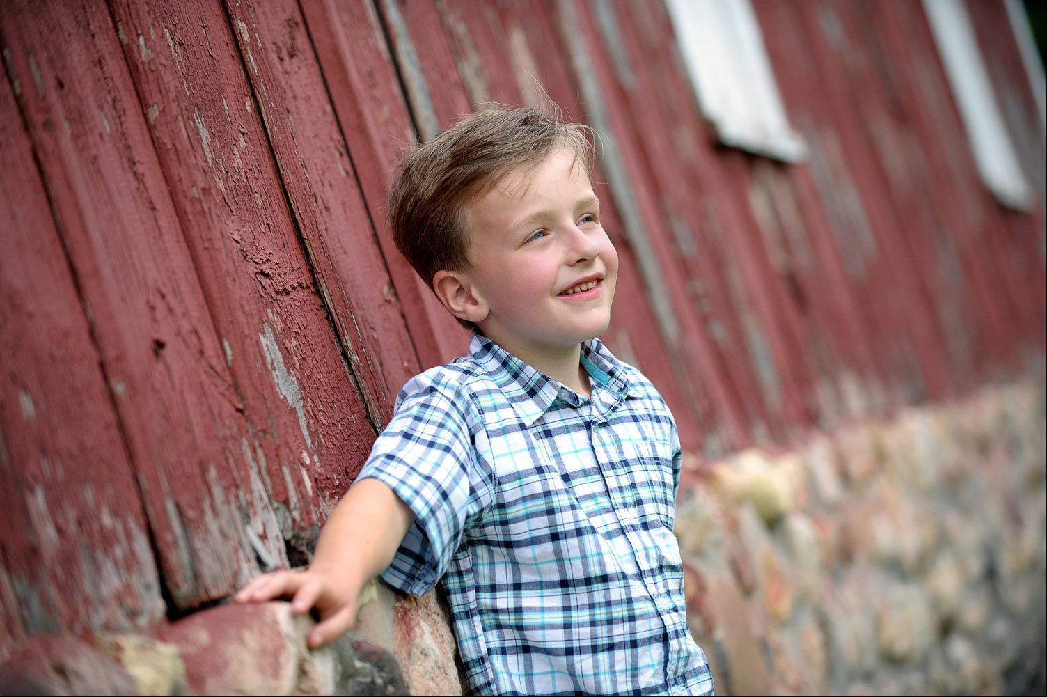 Once your kids are old enough to pose for you, the options for backgrounds become endless. In this case, Laura used a telephoto lens and minimal depth of field to keep the focus on the subject, even while adding the color and texture of the barn in the background.