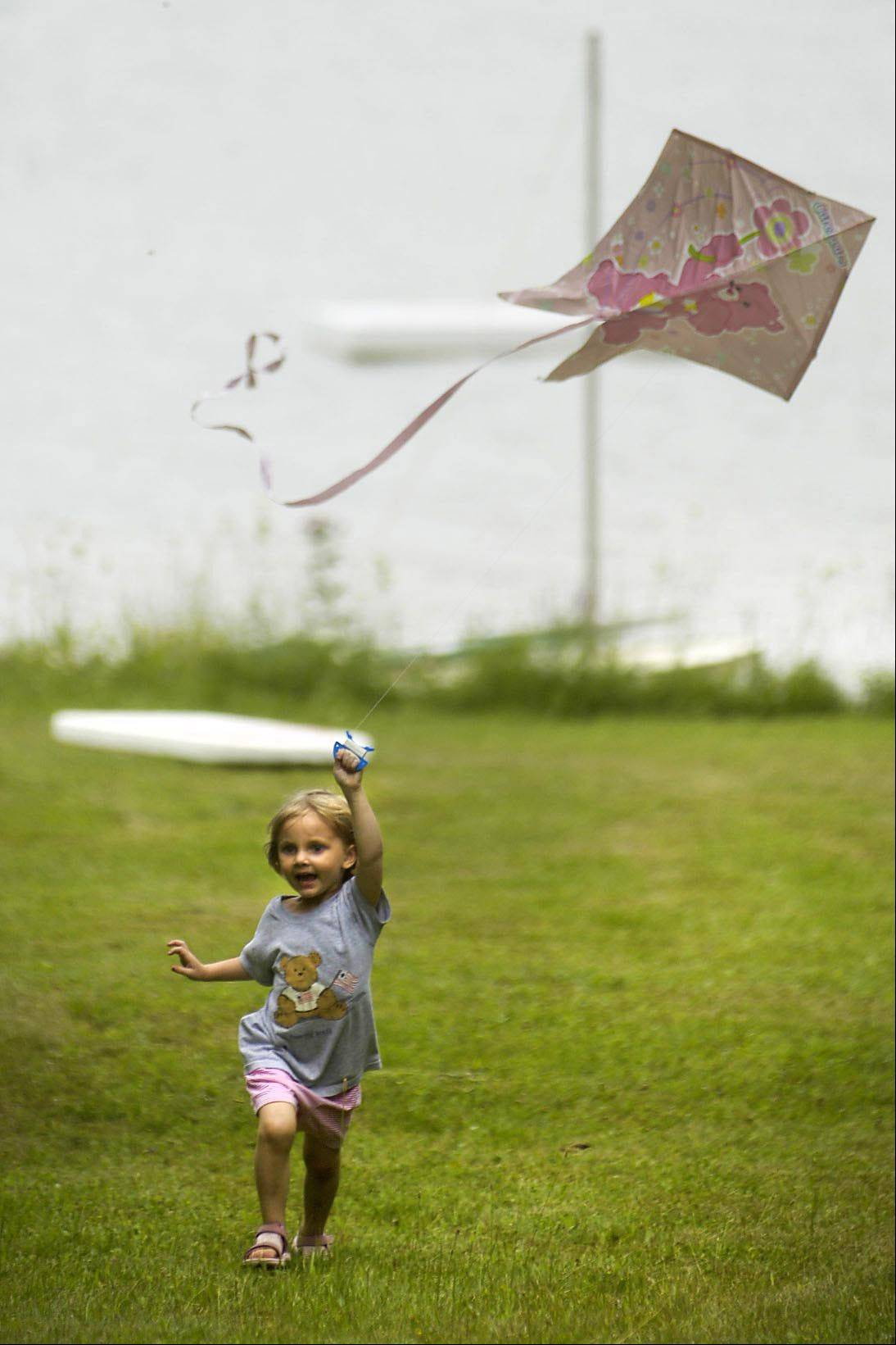 Sometimes you just have to envision what's going to happen and be in the right place to capture the moment. With his daughter, Natalie, running at him and using a telephoto lens, John framed this picture vertically to emphasize the kite as well as his excited daughter.