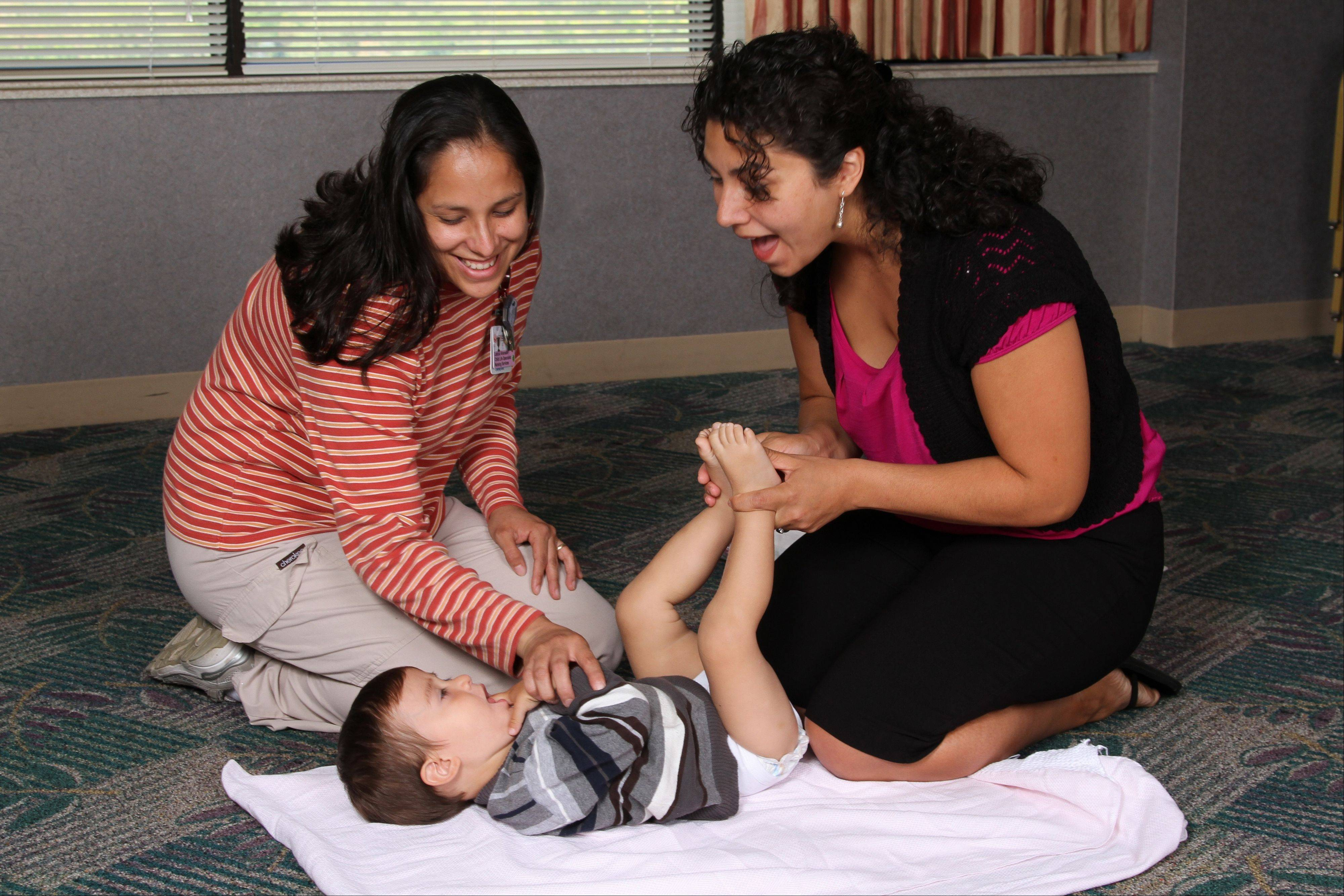 Martha Valdez of Schaumburg learned infant massage after her son Daniel was born. Leticia Alvarado, left, is a certified infant massage educator for St. Alexius Medical Center.