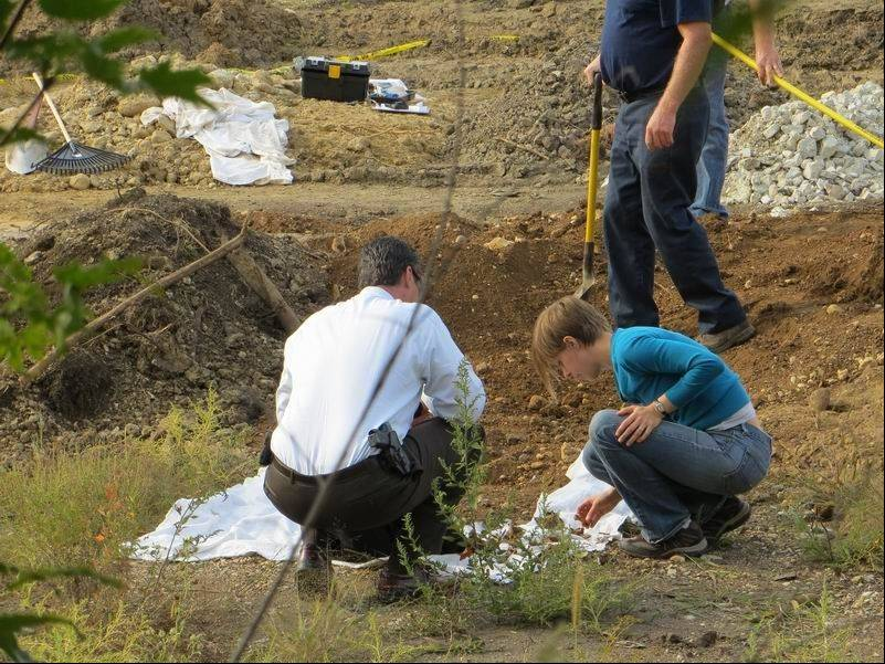 Investigators examine skeletal remains found in a dirt pile in West Chicago on Sept. 25. A woman on a walk discovered the remains, which were determined to be about 100 years old and had been accidentally dug up from an unmarked grave in Aurora.