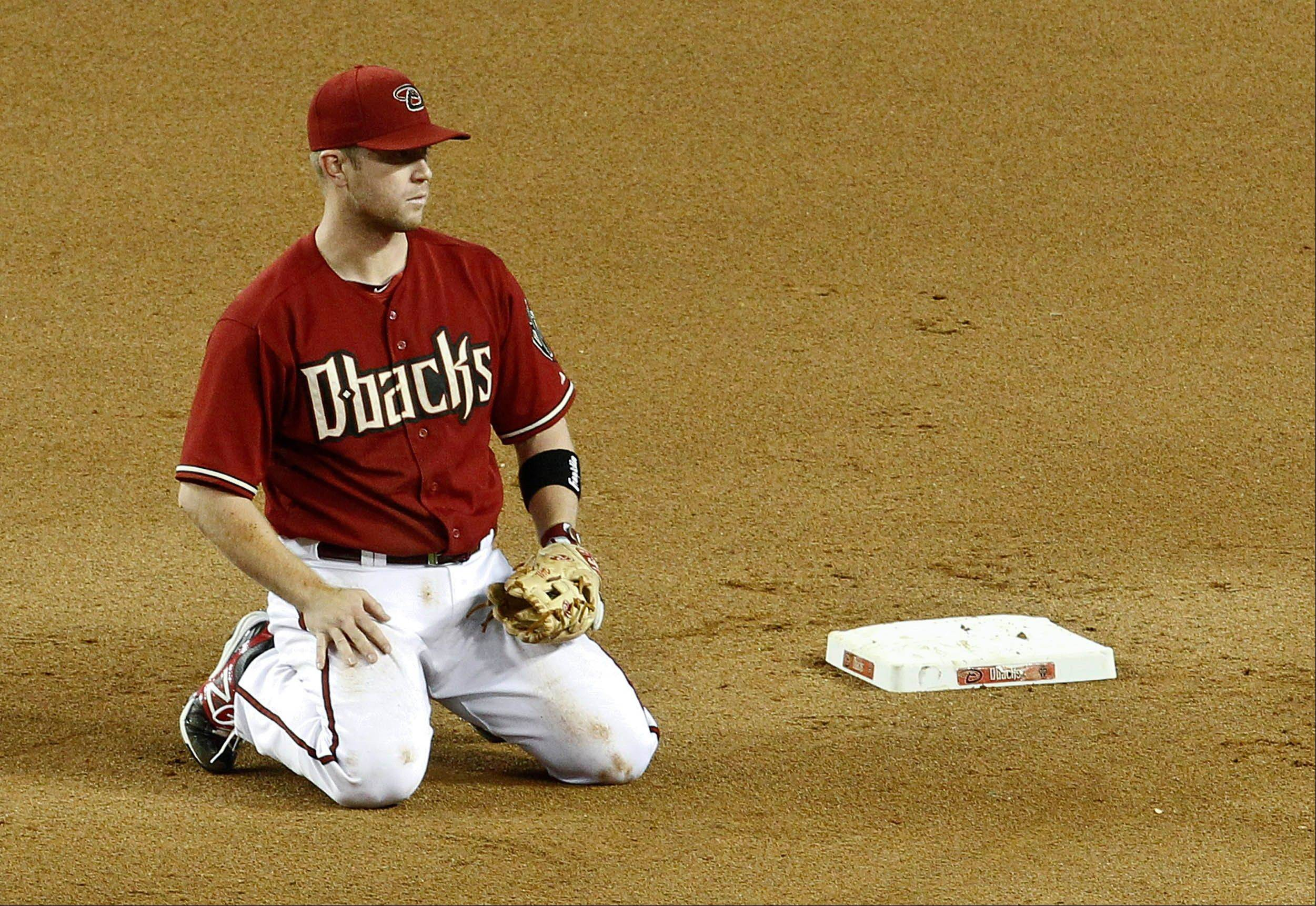 Arizona's Aaron Hill kneels after teammate Chris Johnson threw wildly to him at second base, resulting in an error for Johnson and a run for the Colorado Rockies on Wednesday in Phoenix.