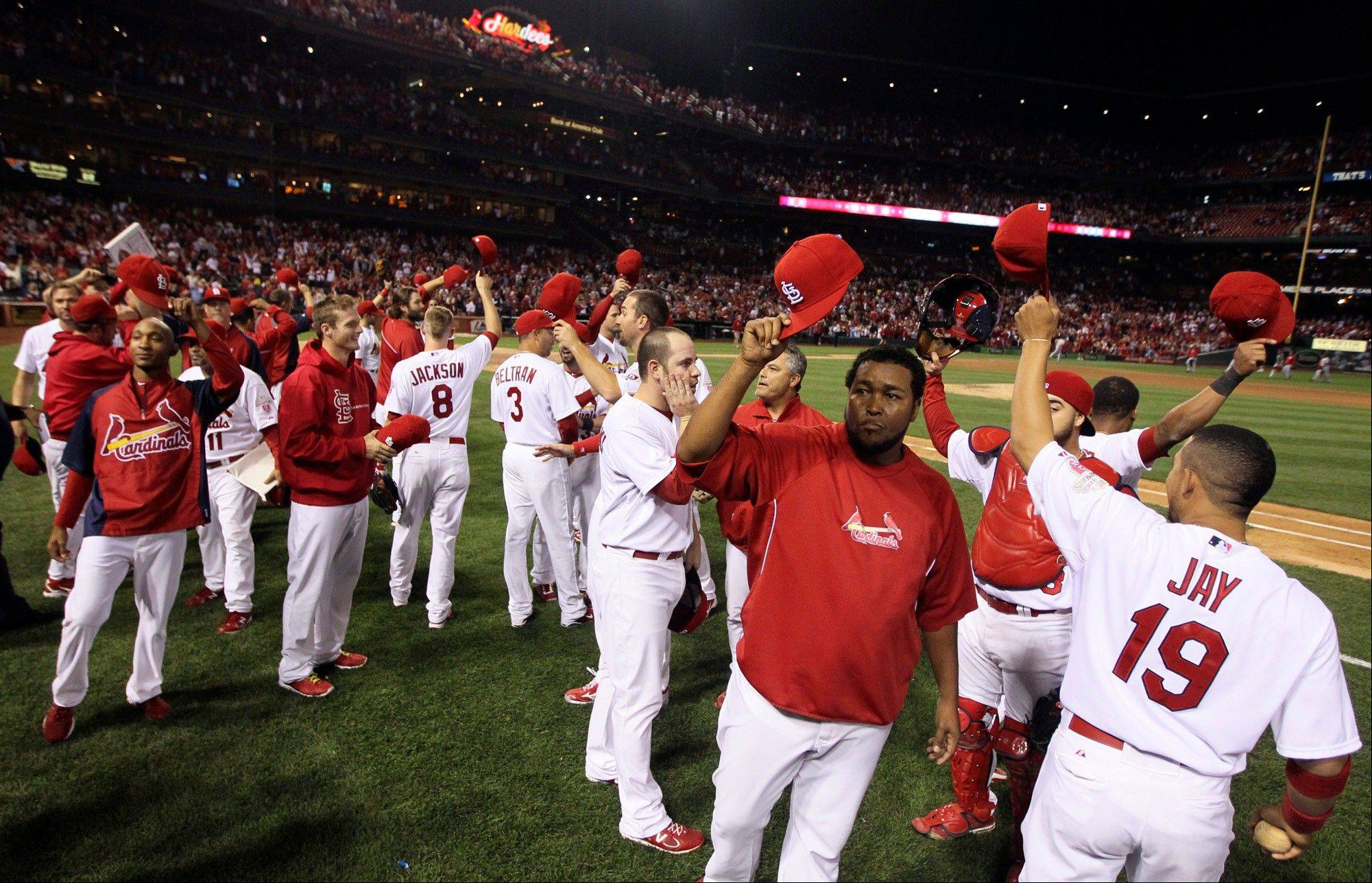 St. Louis Cardinals players wave their caps to acknowledge the fans after their win over the Cincinnati Reds on Wednesday at home.
