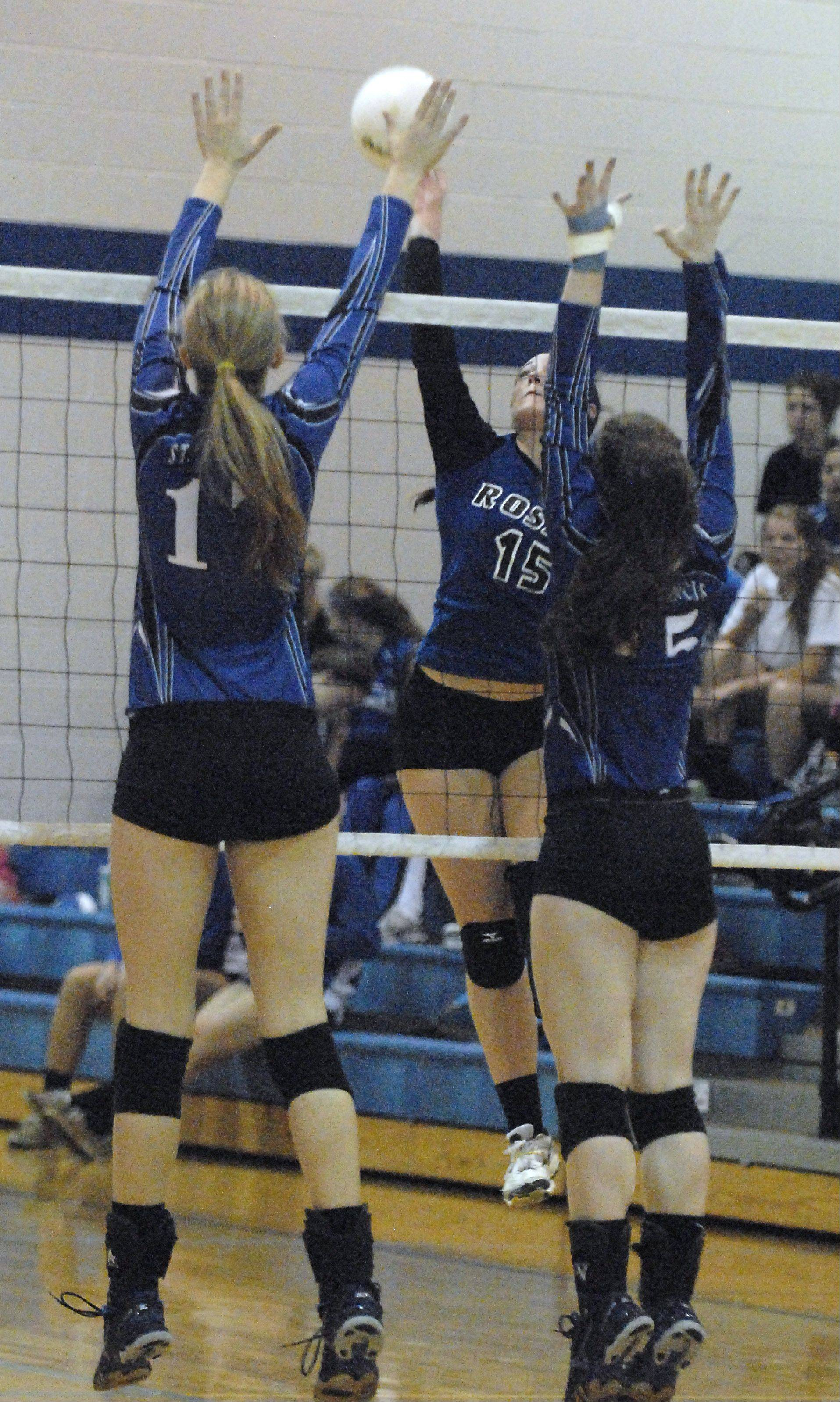 Laura Stoecker/lstoecker@dailyherald.comRosary's Erin Bowe spikes the ball over St. Francis' Mary Boken and McKenna Kelsay in the first game on Wednesday, October 3.