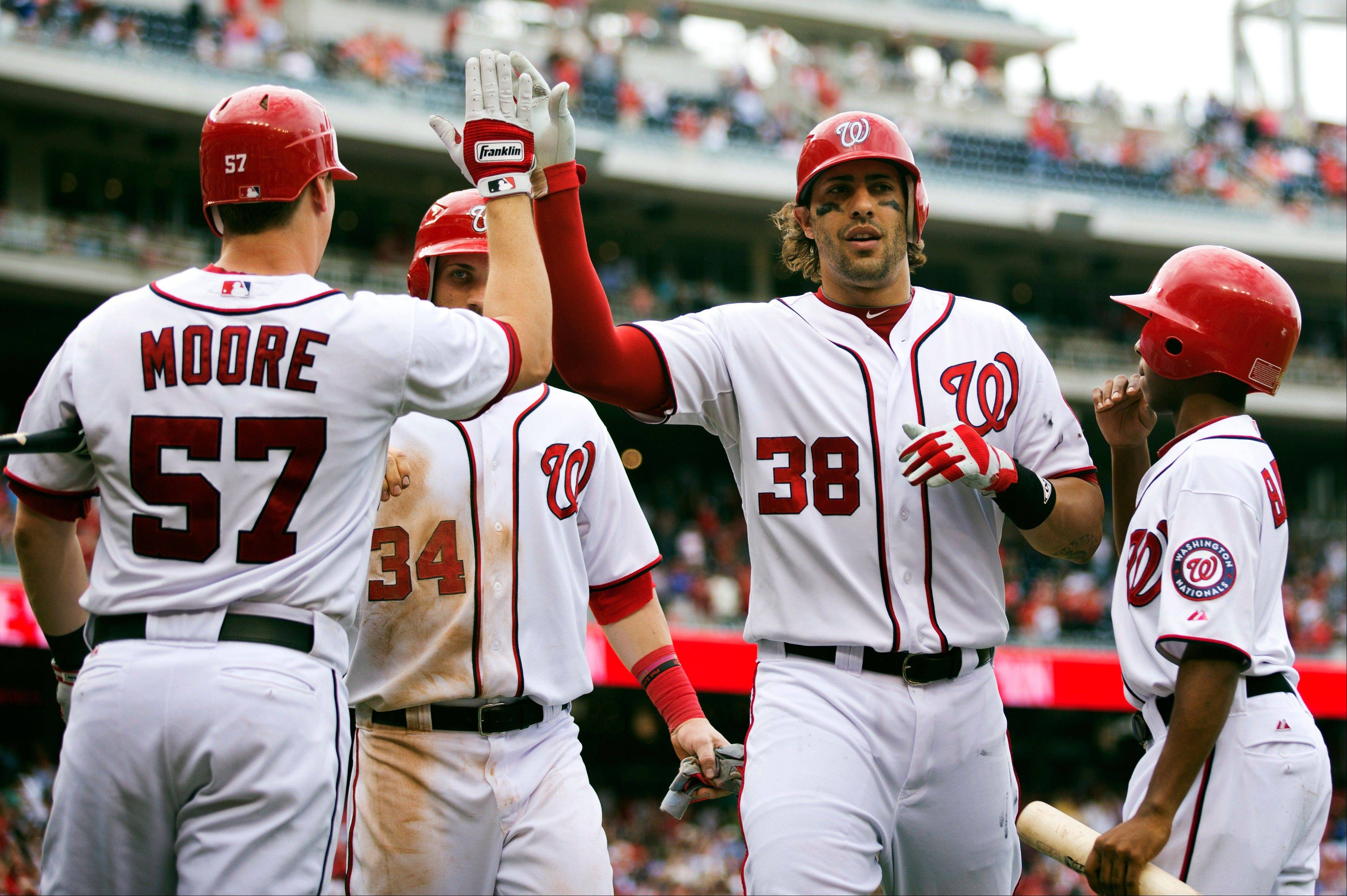 Washington's Michael Morse (38) is congratulated by Tyler Moore (57) after hitting a home run during the eighth inning Wednesday at home against Philadelphia.