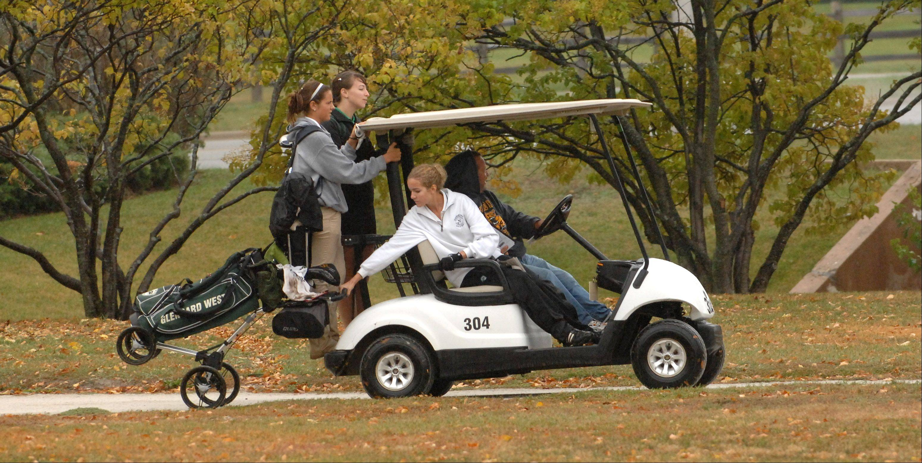 A soaking rain dogged the golfers at Wednesday's York girls golf regional at Maple Meadows Golf Course in Wood Dale. From left, Tessa Dittmann from West Chicago, Kerri Carlquist from York, and Emma Klimala from Glenbard West, get a lift from the 3rd green to the 4th tee in the rain.
