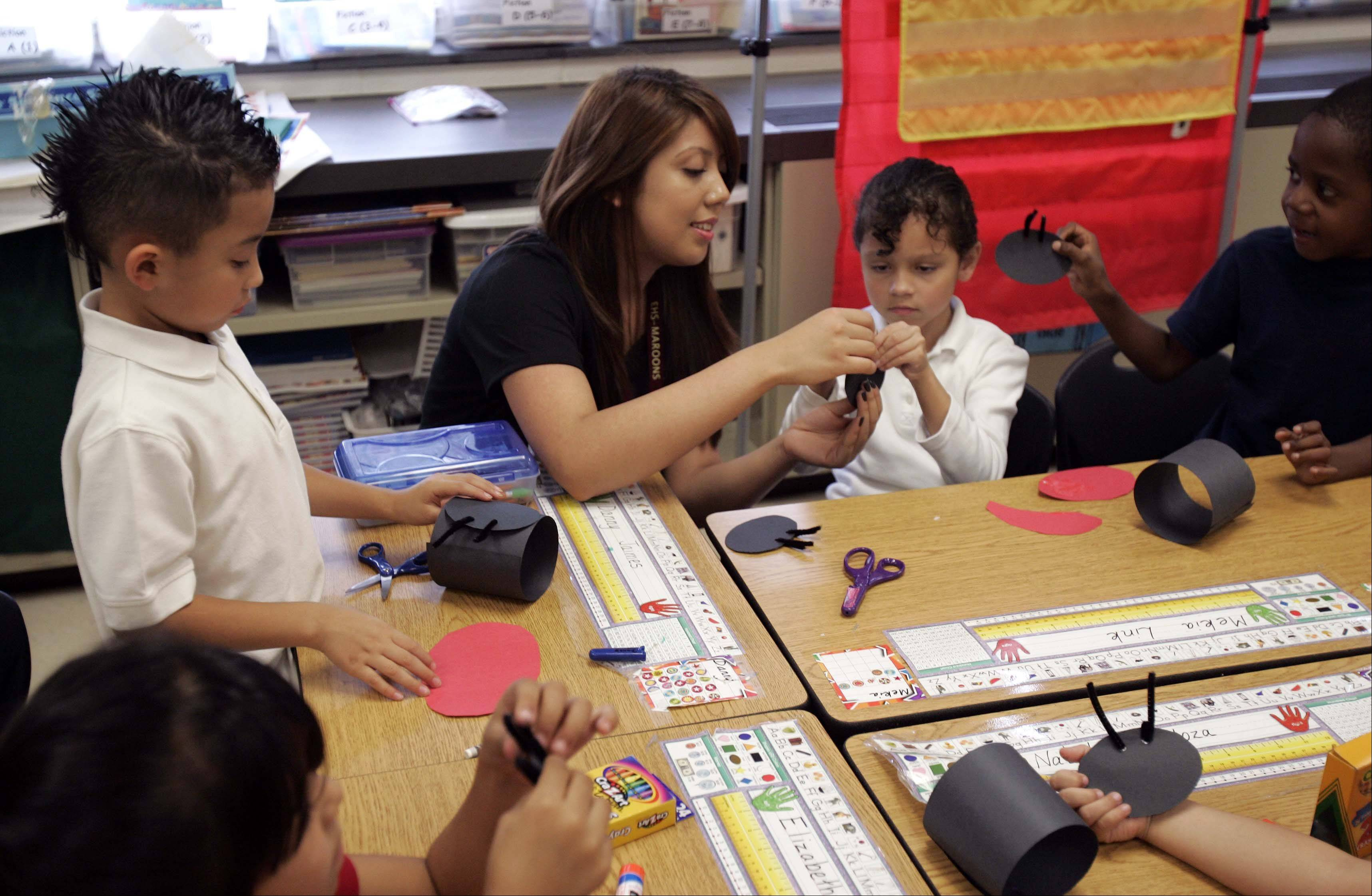 "Maria Garcia, a member of the Future Teachers of America Club from Elgin High School, shows students in Mrs. Ramos' first-grade class at Huff Elementary School in Elgin how to make a ladybug from construction paper during a lesson Wednesday. The high school students read ""Ladybug Girl and the Bug Squad"" to students as part of the national Read for the Record campaign."
