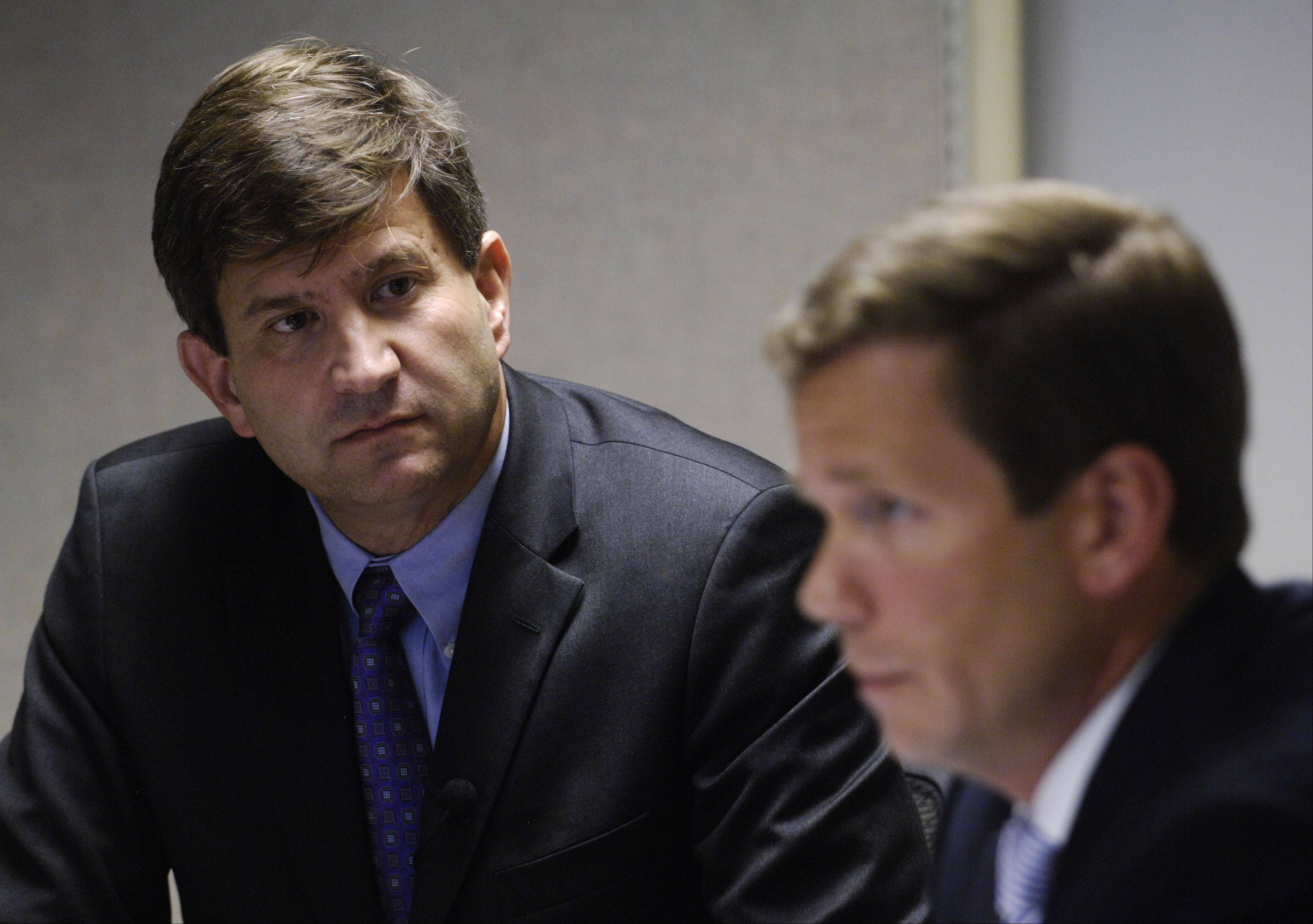 Brad Schneider, left, listens to Robert Dold speak to reporters and editors at the Daily Herald.
