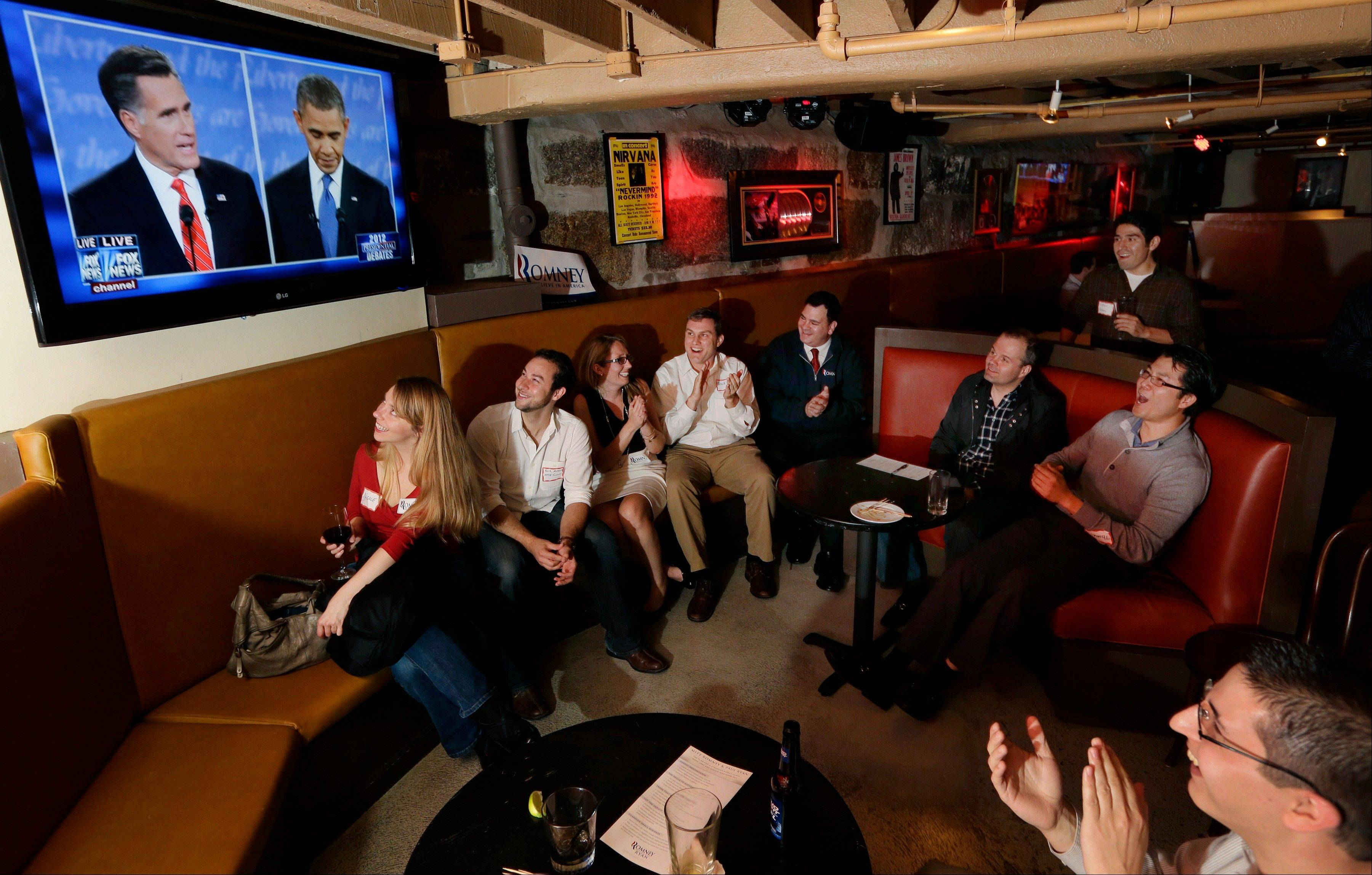 Members of the Massachusetts GOP Young Republicans react as they watch the first presidential debate between President Barack Obama and Republican Mitt Romney, Wednesday, Oct. 3, 2012, in Boston.