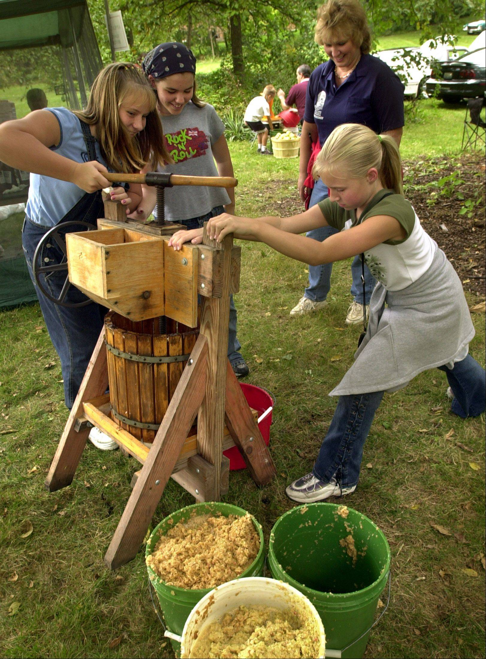 During Harvest Time, weekend visitors to Naper Settlement can try their hand at working a cider press and take part in other pioneer-era activities.