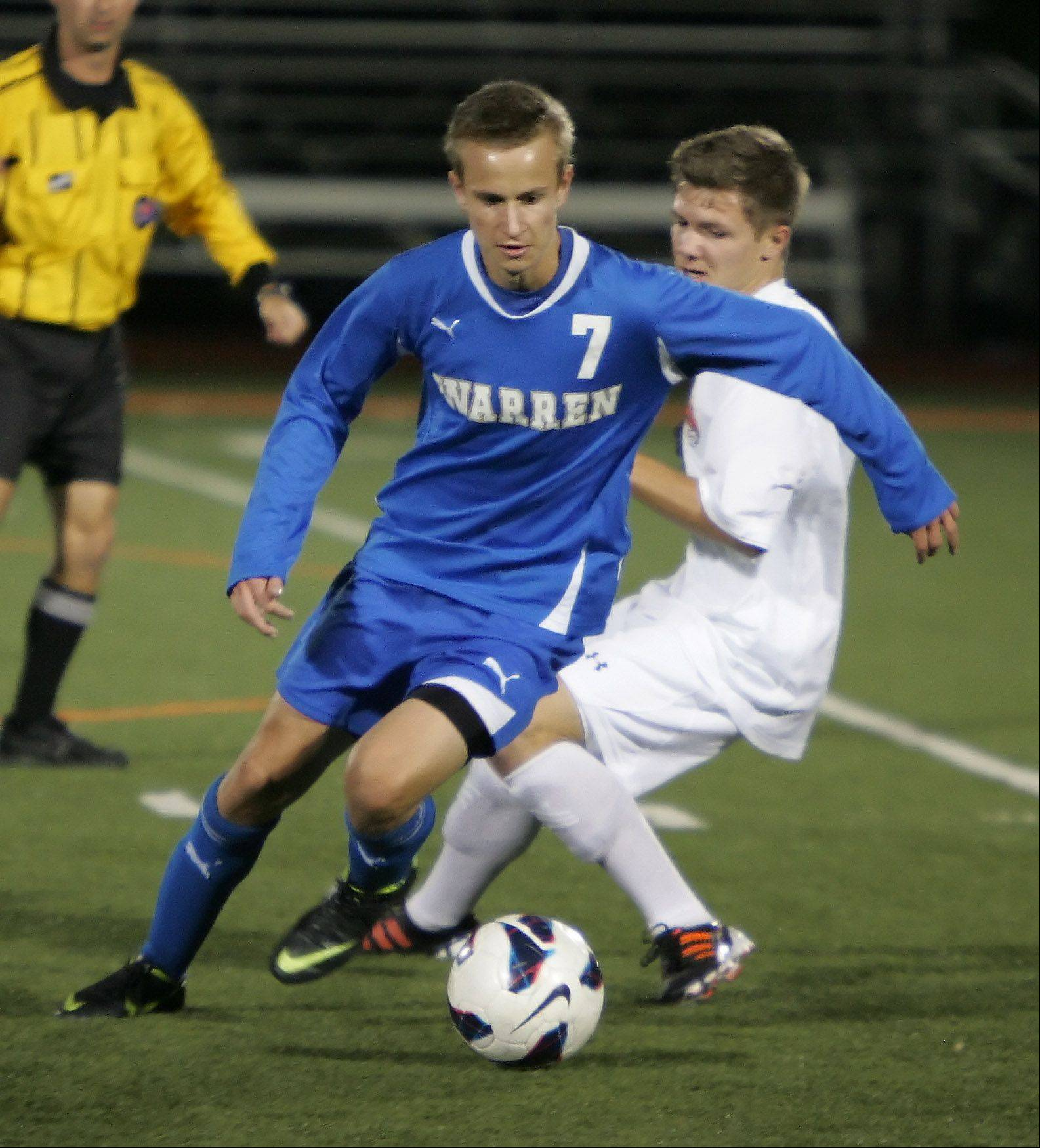 Warren midfielder Nick Wegrznowicz moves around Libertyville's Rahf Zehnter on Thursday at Libertyville.