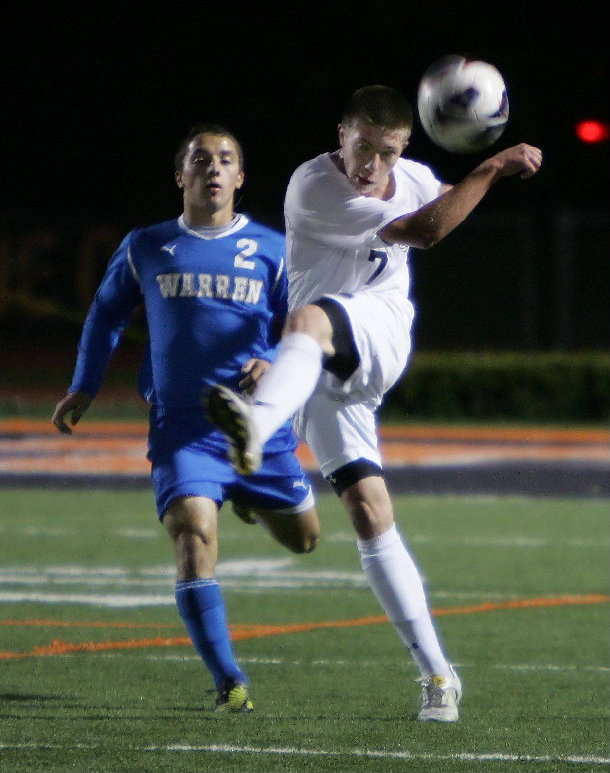 Libertyville midfielder Nick Vogel kicks the ball down field as Warren's Tony Severini rushes up on Thursday at Libertyville.
