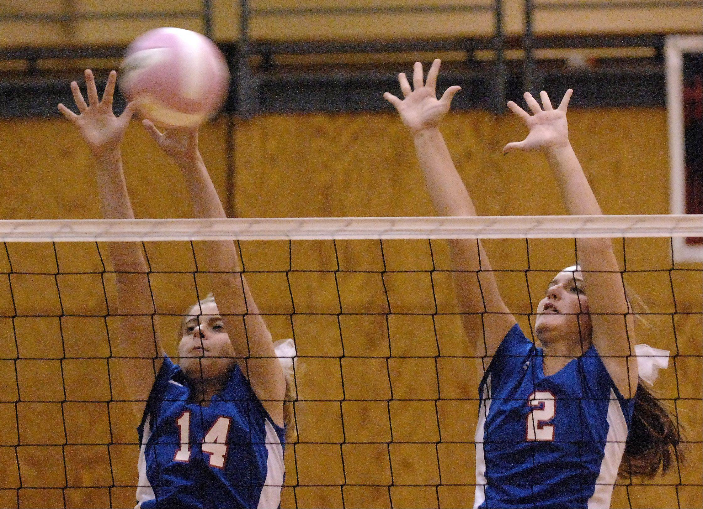 Glenbard South's Tomei Ball, left, and Laura Quinlivan go up for a block against Batavia during Thursday's game at Batavia.