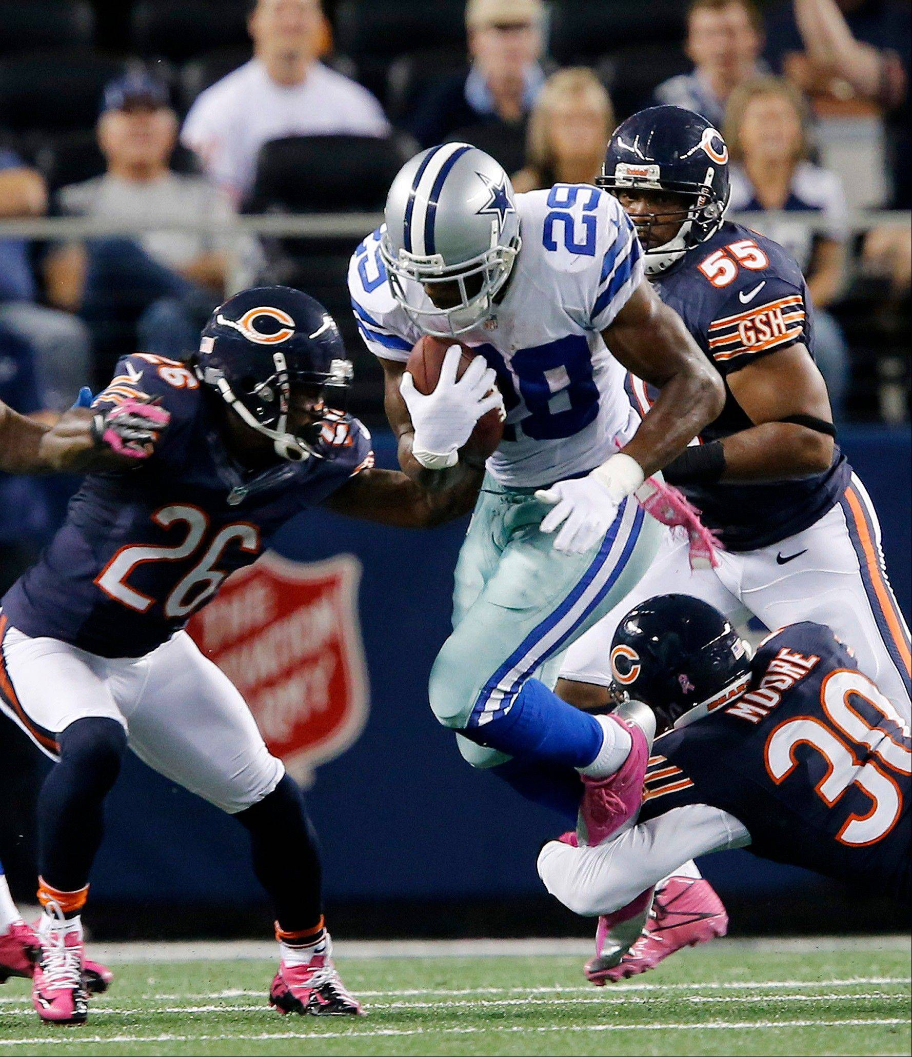 Tim Jennings (26) combines forces with D.J. Moore to tackle Cowboys running back DeMarco Murray on Monday in Dallas. Jennings was named the NFC defensive player of the month for September.