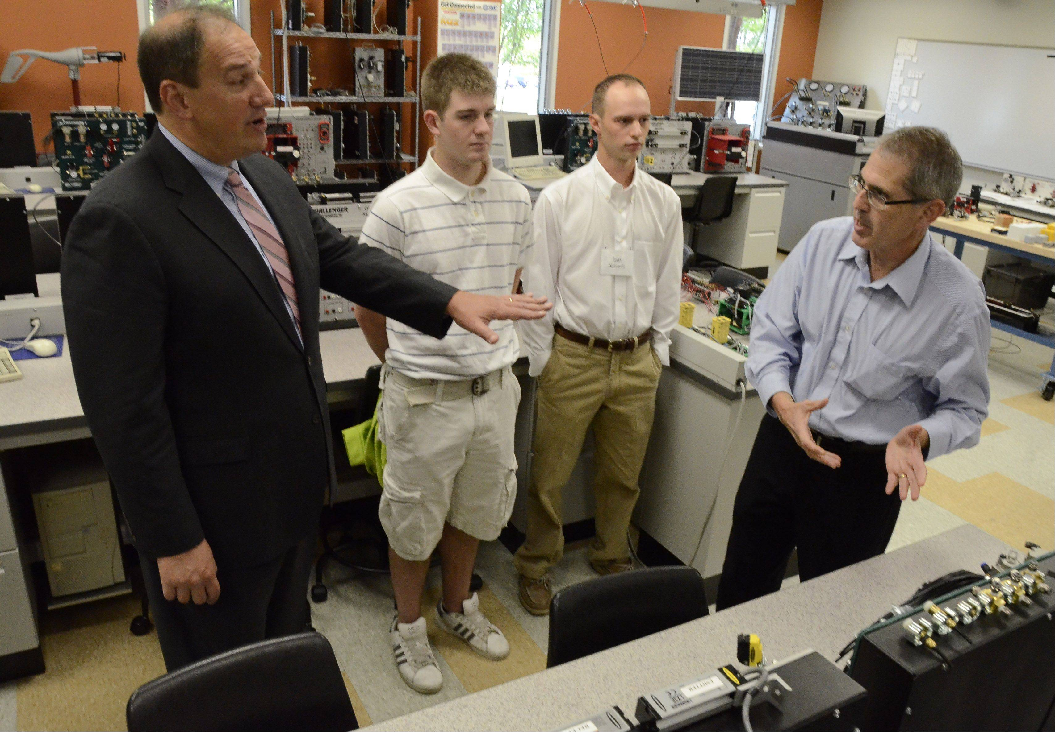 U.S. Department of Labor Deputy Secretary Seth Harris, from left, talks with students Curtis Willuweit of Hoffman Estates, Ian Mitchell of Deer Park and assistant professor Samuel Levenson while visiting one of Harper College�s mechatronics labs.