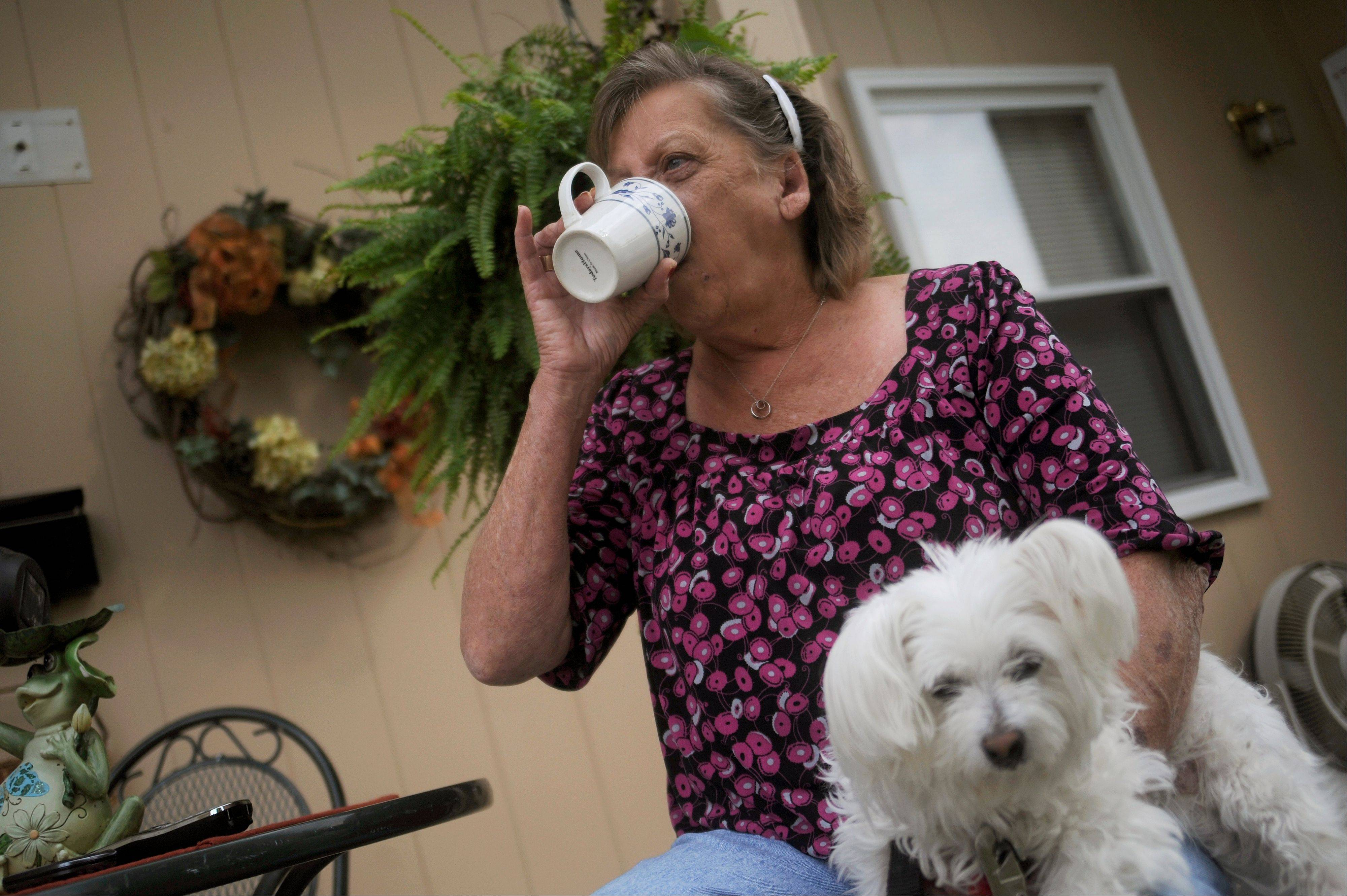 Patsy Bivins, 68 of Sturgis, Ky., drinks coffee Friday while sitting on her porch with her dog, Little Britches, at her apartment in Sturgis, Ky. Bivins was injected with steroids at St. Mary Sugricare in Evansville, Ind., who notified her of possibly being infected with bacterial Meningitis.