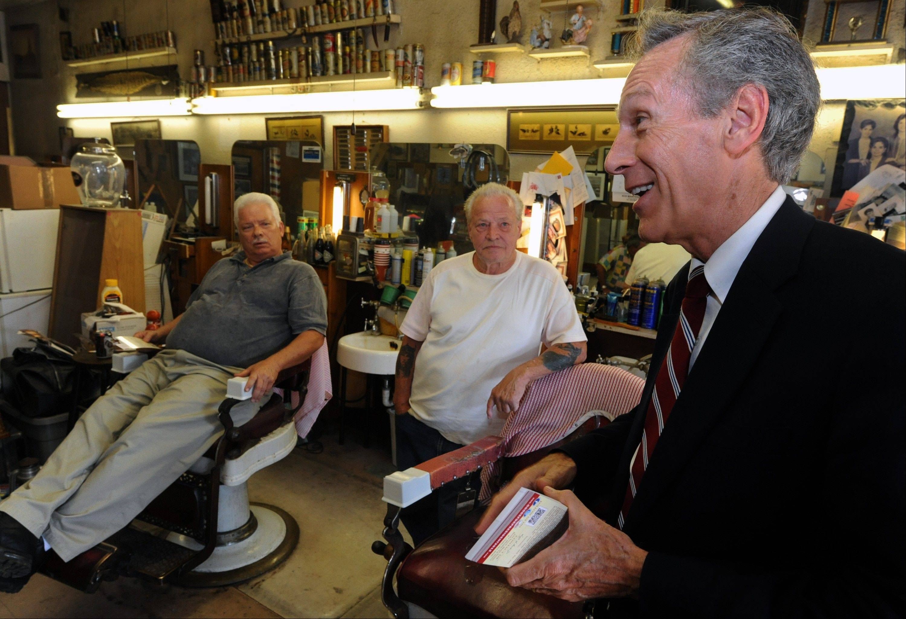 Constitution Party presidential candidate Virgil Goode Jr., right, talks to barber shop owner Alvin Womack, center, and Terry Womack while campaigning in Lynchburg, Va.