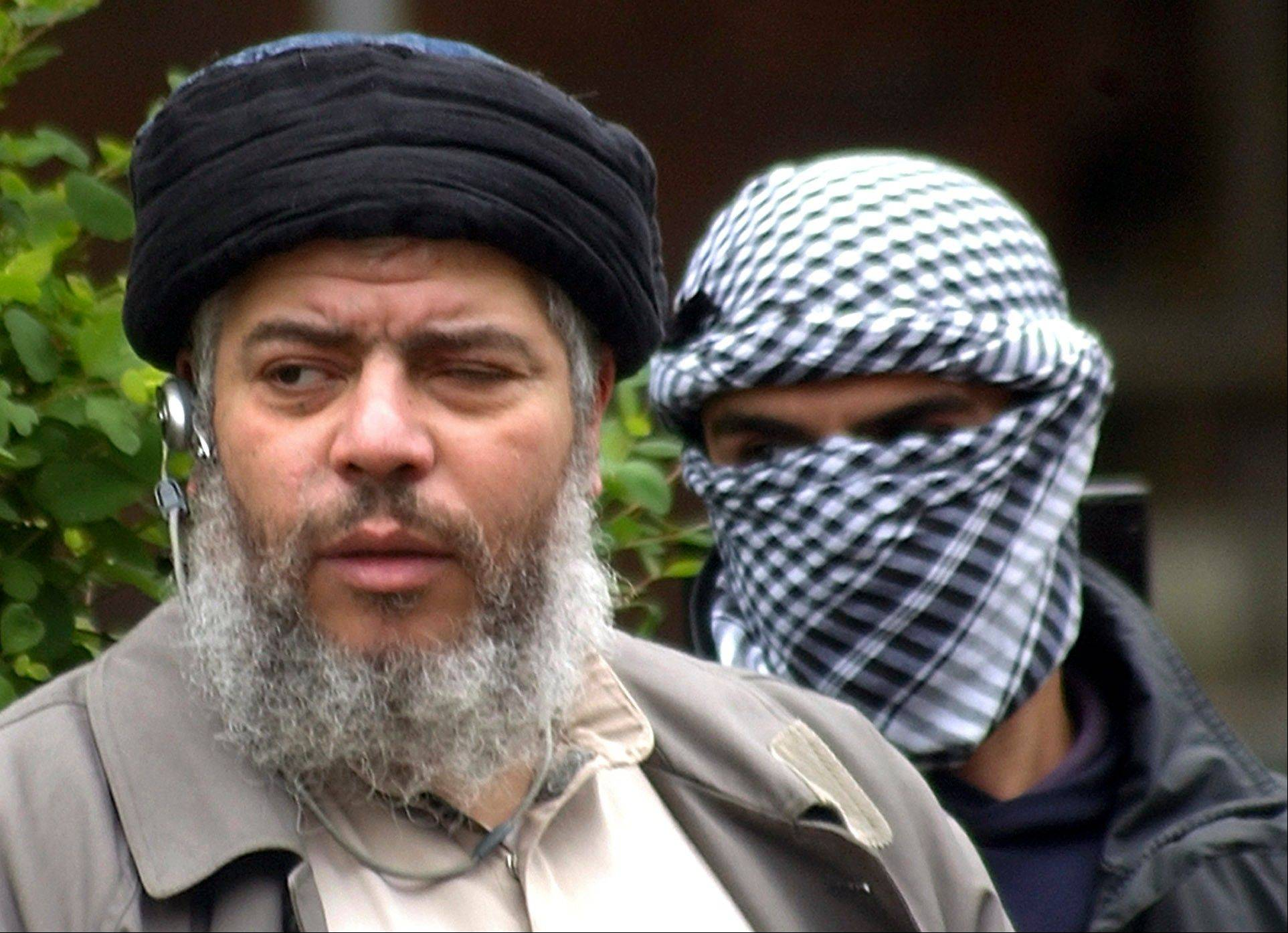 This 2004 file photo shows Muslim cleric Abu Hamza al-Masri, as he arrives with a masked bodyguard, right. A British court ruled Friday that al-Masri and four other terror suspects can be extradited immediately to the U.S. to face charges there.