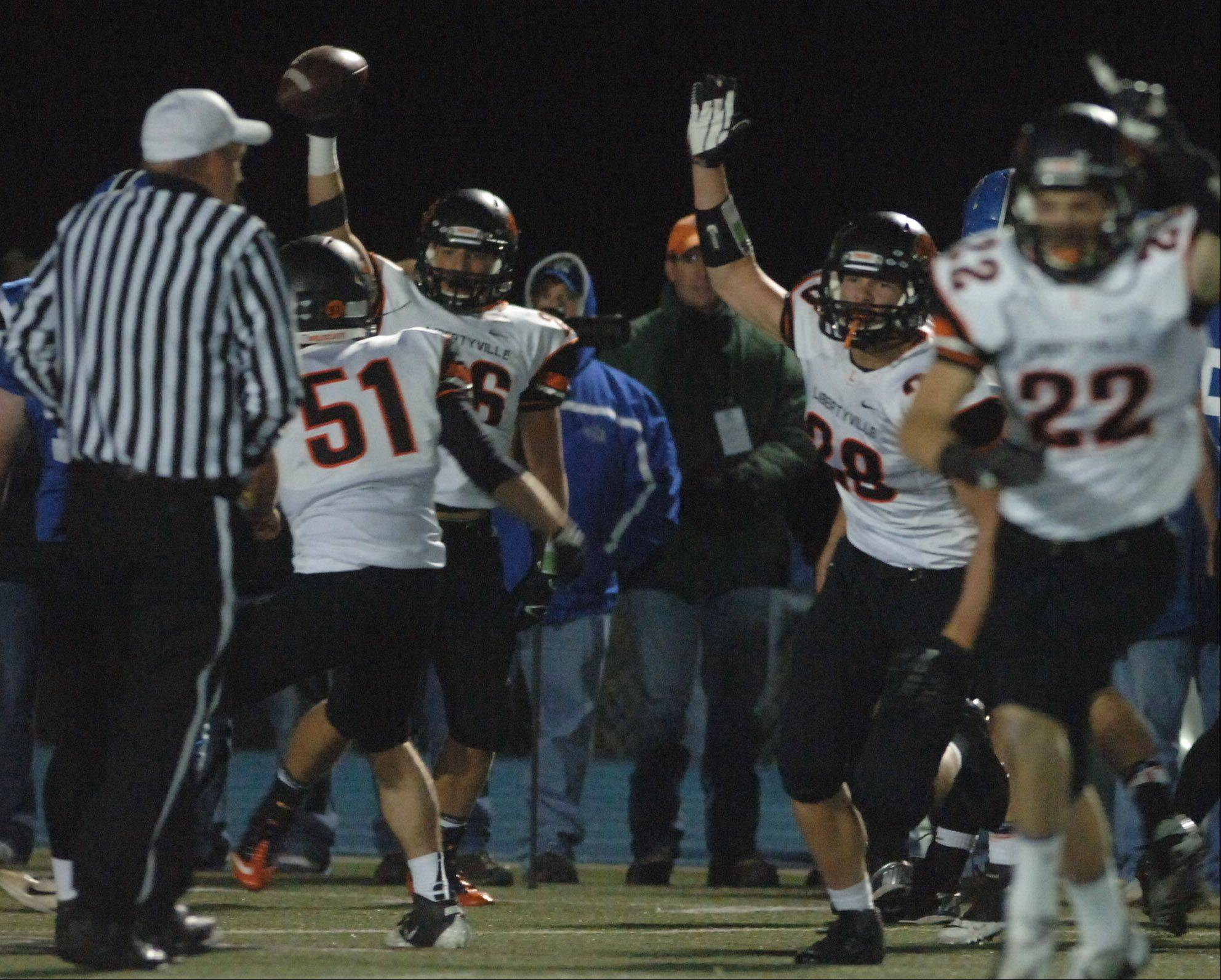 Libertyville players celebrate after coming up with a fumble recovery in the second half of a 3-0 triumph Friday at Lake Zurich.
