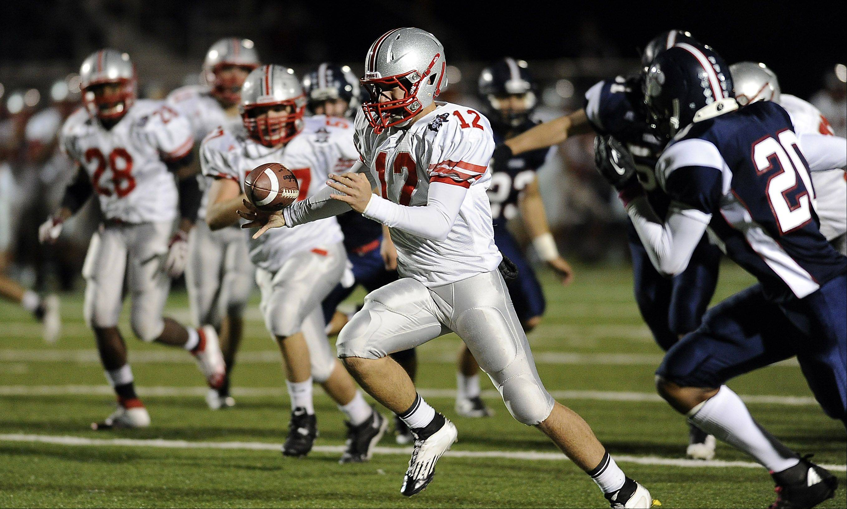 Palatine�s quarterback Ethan Olles tries to maintain control of the ball as he runs.