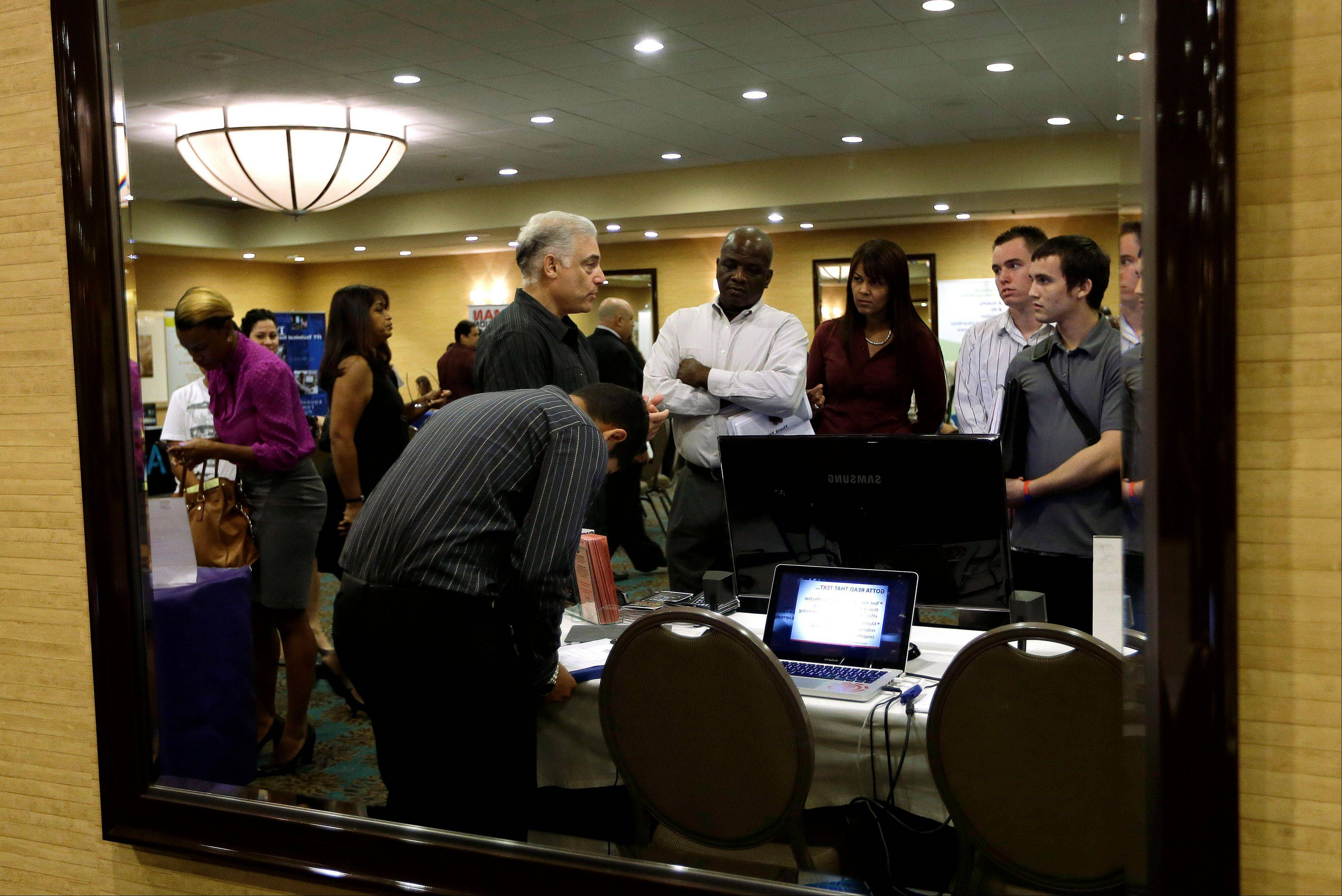 Robert Orkin, of the company TxT-Alert, third from left, talks with job seekers during a job fair held by National Career Fairs, in Fort Lauderdale, Fla.