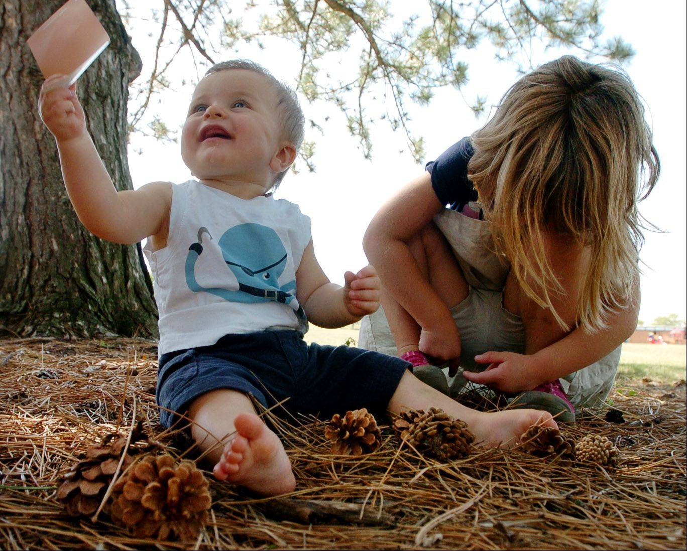 10-month-old Benjamin discovers pine cones with his sister Lily, that match his color swatch in Hoover Park during their nature hike.