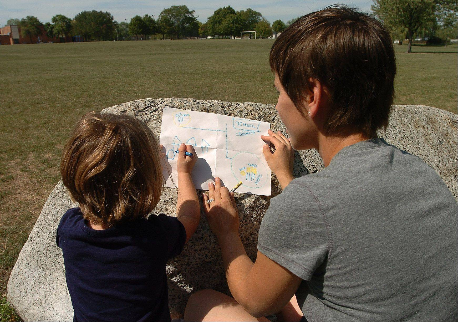 Lily and Rebecca Anderson check off on a map what they've found along their nature hike in Hoover Park.