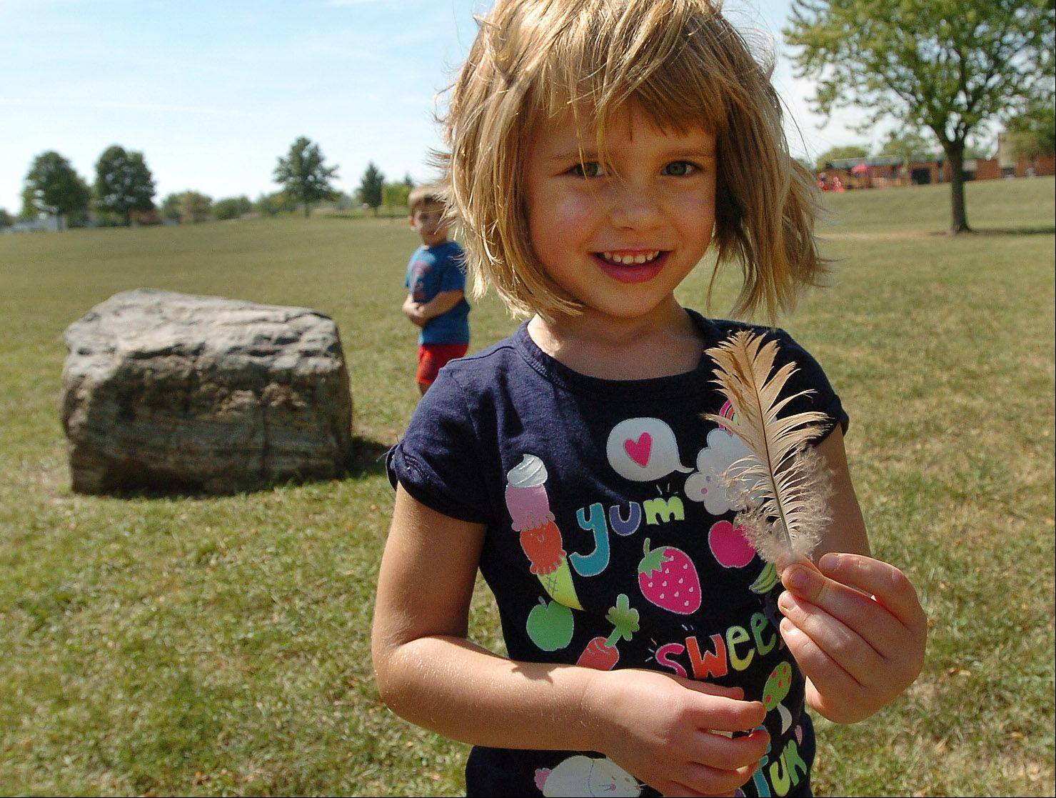 4-year-old Lily Anderson finds a feather in Hoover Park along her nature hike.