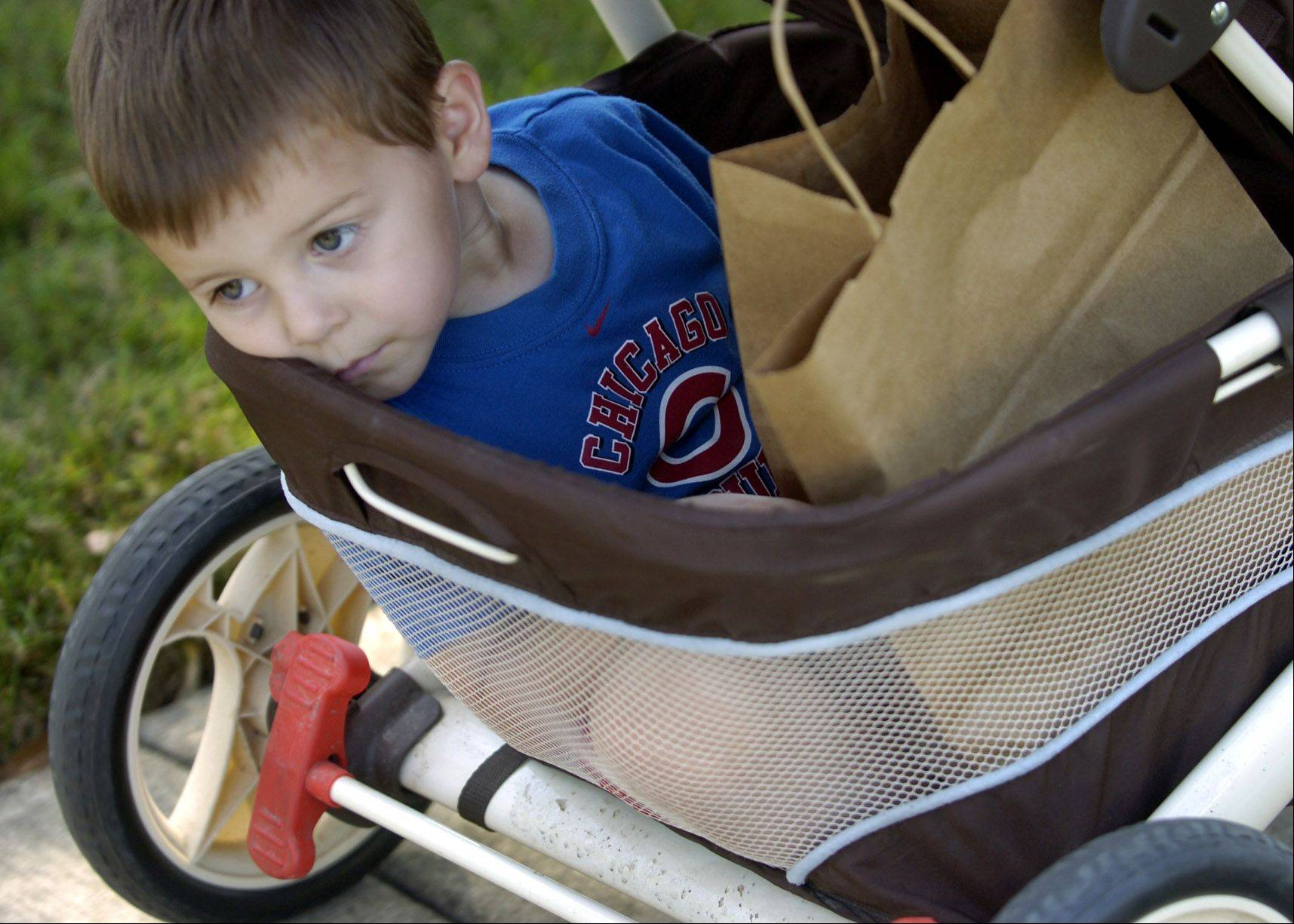3-year-old Justin Anderson hitches a ride on the back of baby Ben's stroller, on the way back from their nature hike.