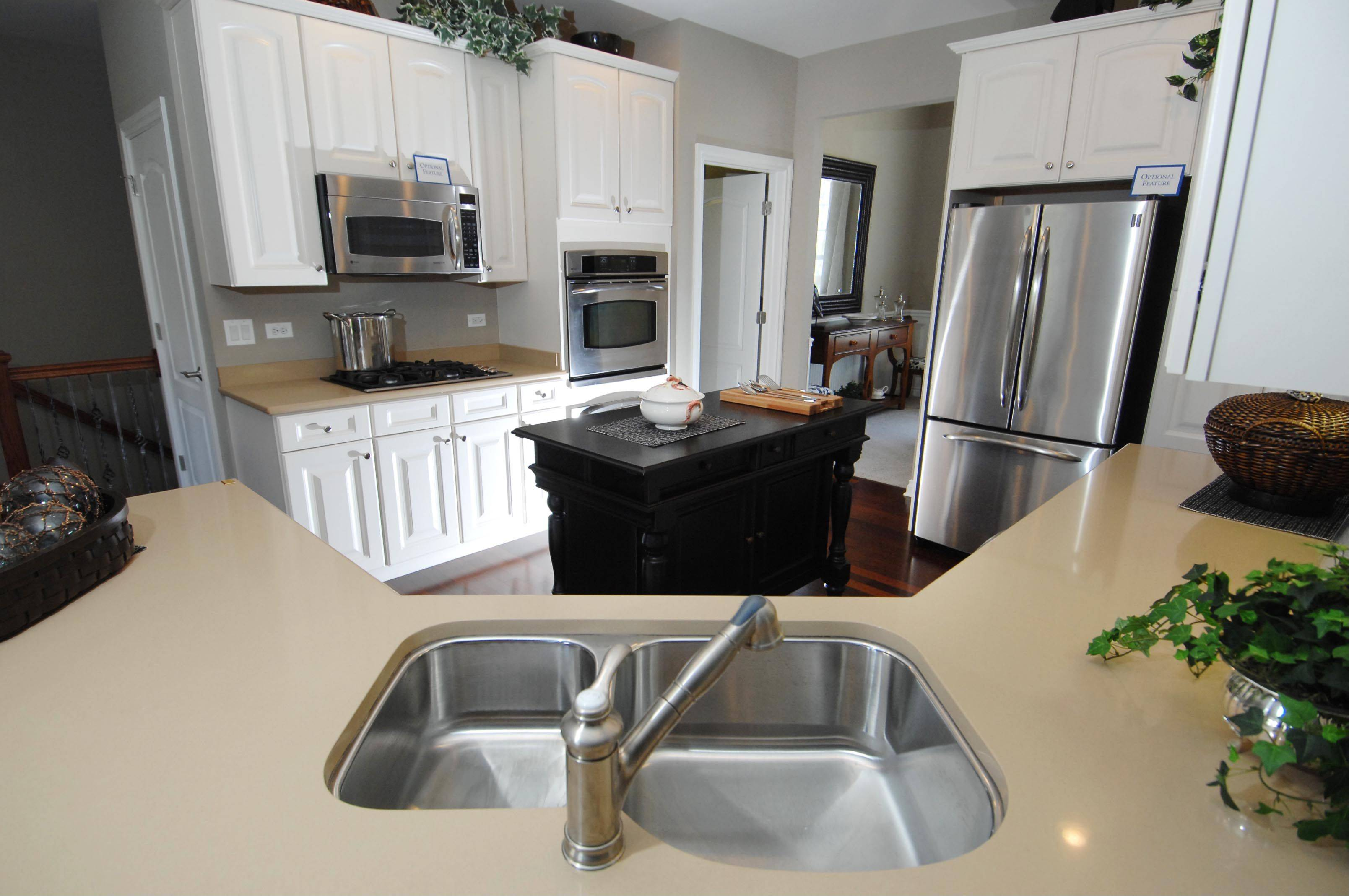 The kitchen of the Jefferson model features stainless steel appliances and sink, and a large black island and white cabinets at Liberty Trails in McHenry.