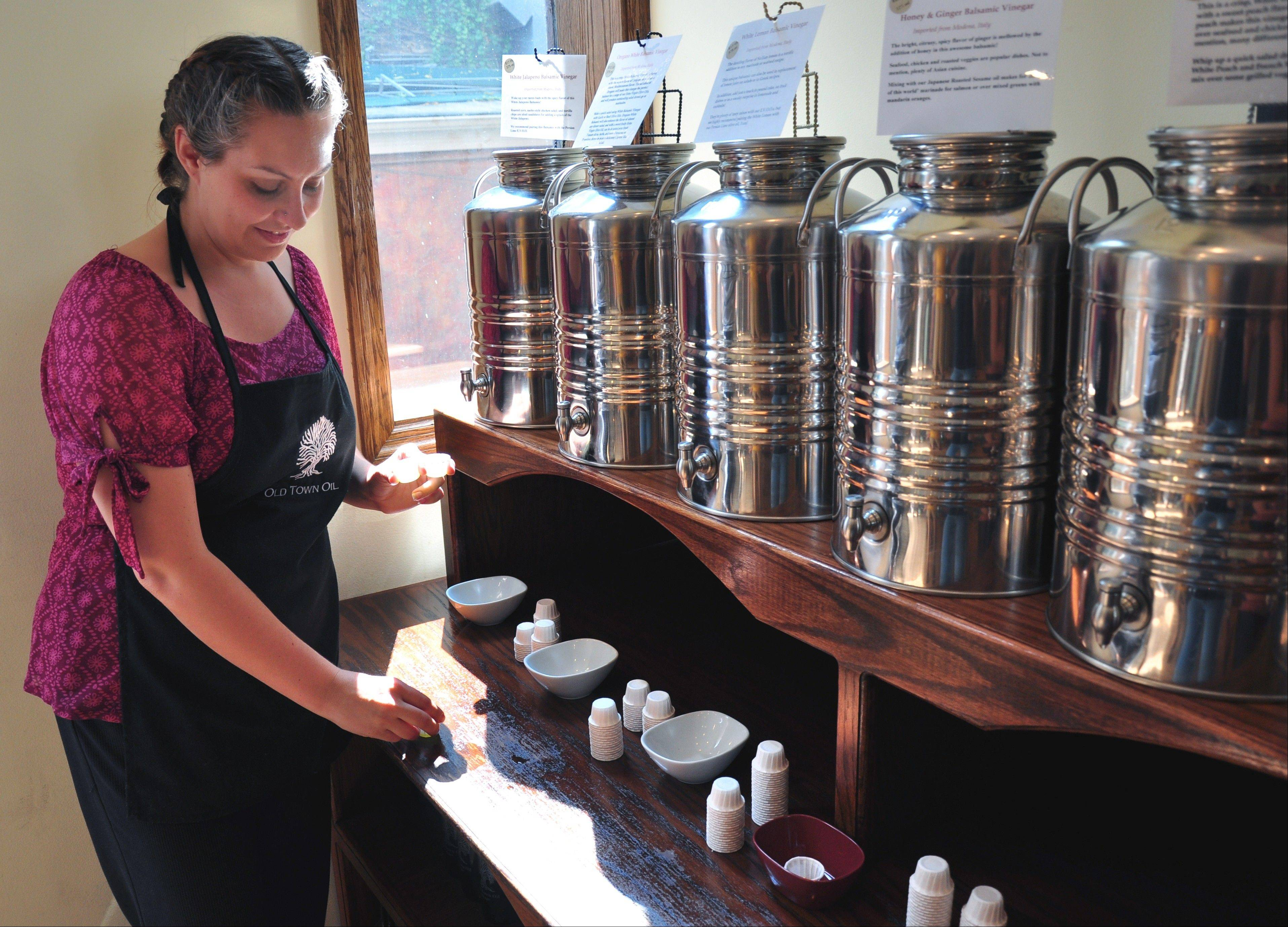 An Old Town Oil employee tends to containers of flavored balsamic vinegar for tasting.