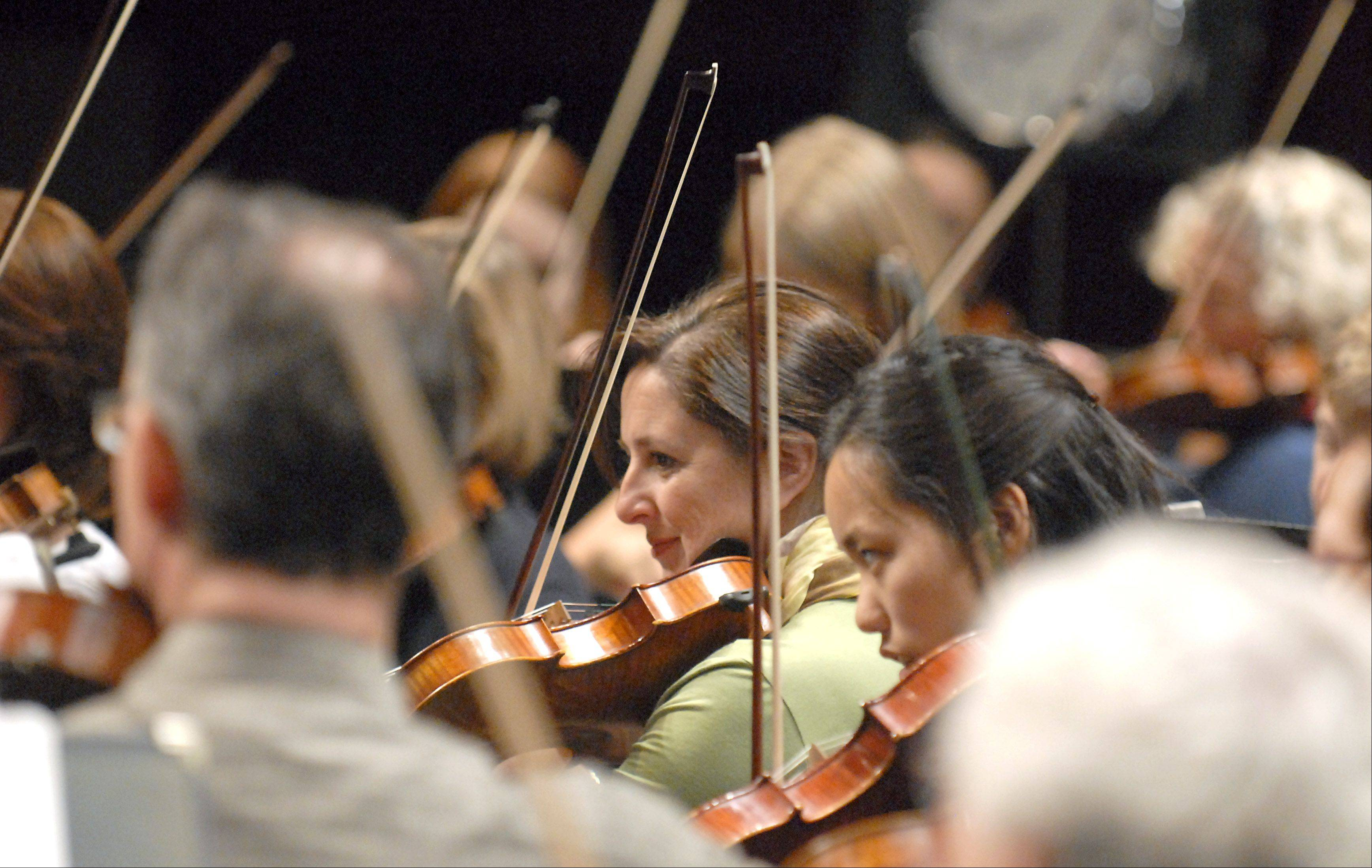 Violinists perform a piece with the Elgin Symphony Orchestra during rehearsal at the Hemmens Cultural Center in Elgin on Friday. The behind-the-scenes event was offered as a Daily Herald Subscriber Total Access event.