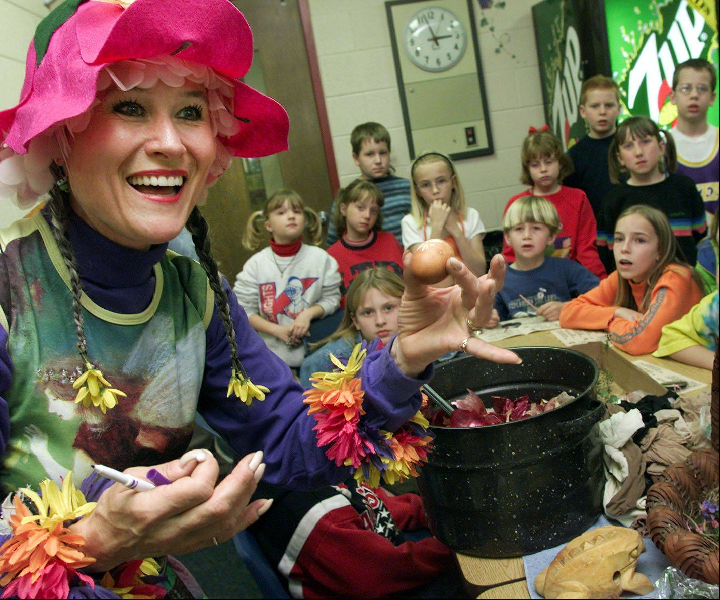 As Mother Nature, Lauing-Finzer holds up a naturally-decorated egg for kids at Kingsley Elementary in Naperville in this file photo.