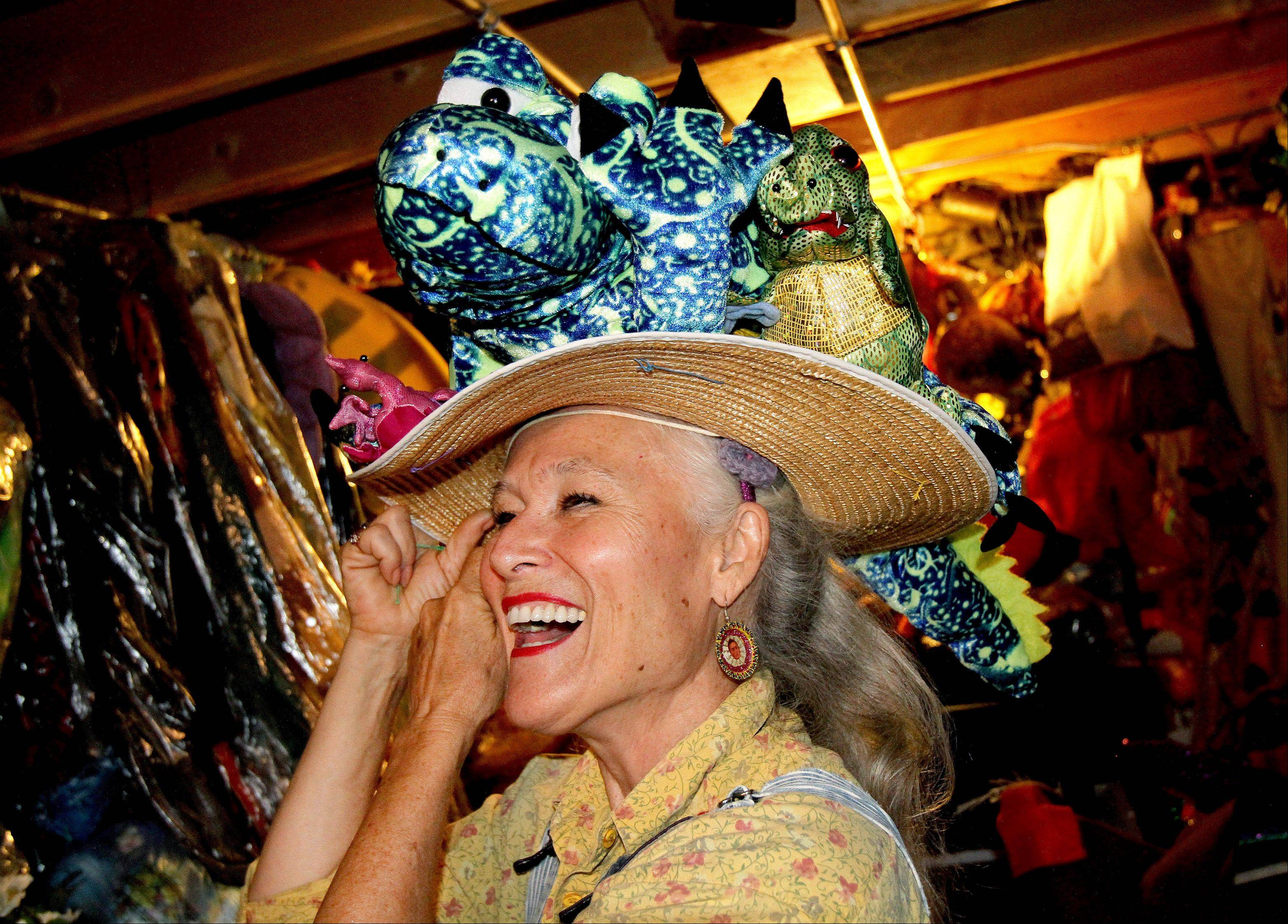 Carolyn Lauing-Finzer of Naperville tries on one of her many costumed hats.