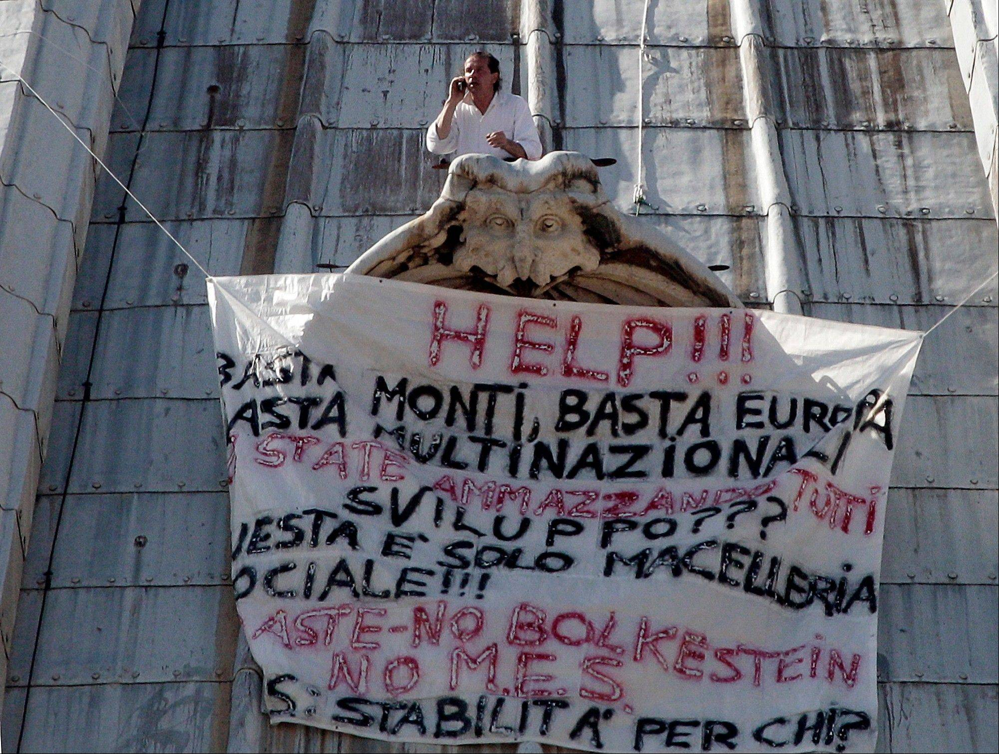 "Italian businessman Marcello di Finizio gave up his protest atop the St. Peter's Basilica on Wednesday evening, after more than 24 hours perched on the 426-foot dome to demonstrate against government reforms. His banner in Italian reads:""Help!! Enough Monti (Italian Premier Mario Monti), enough Europe, enough multinationals, you are killing all of us. Development?? This is a social butchery!!"""