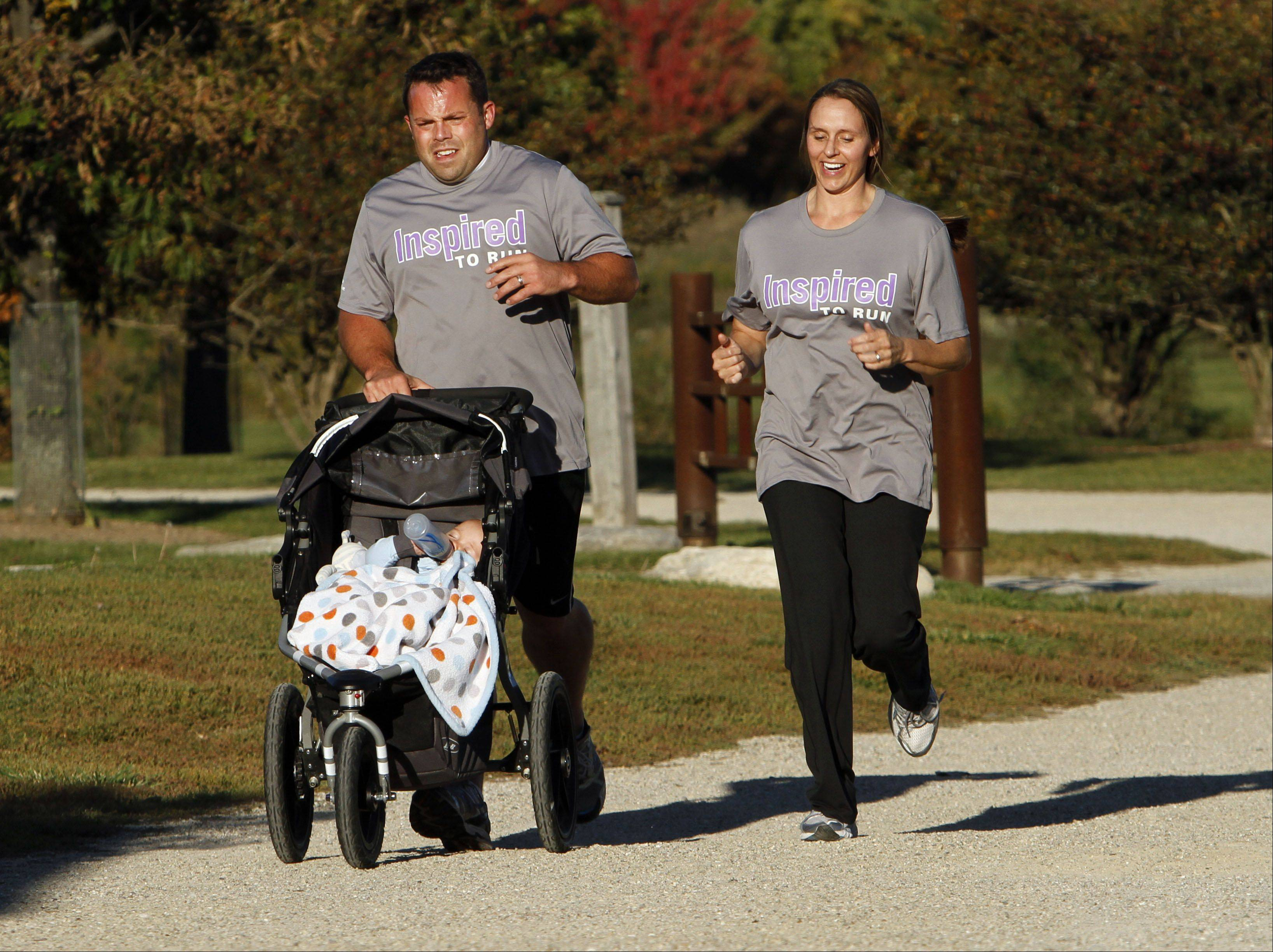 Kirk Disrude and his wife, Beth, train with their 8-month-old son Logan at Independence Grove Forest Preserve in Libertyville. Disrude suffered a stroke last year but is running in Sunday's Bank of America Chicago Marathon.