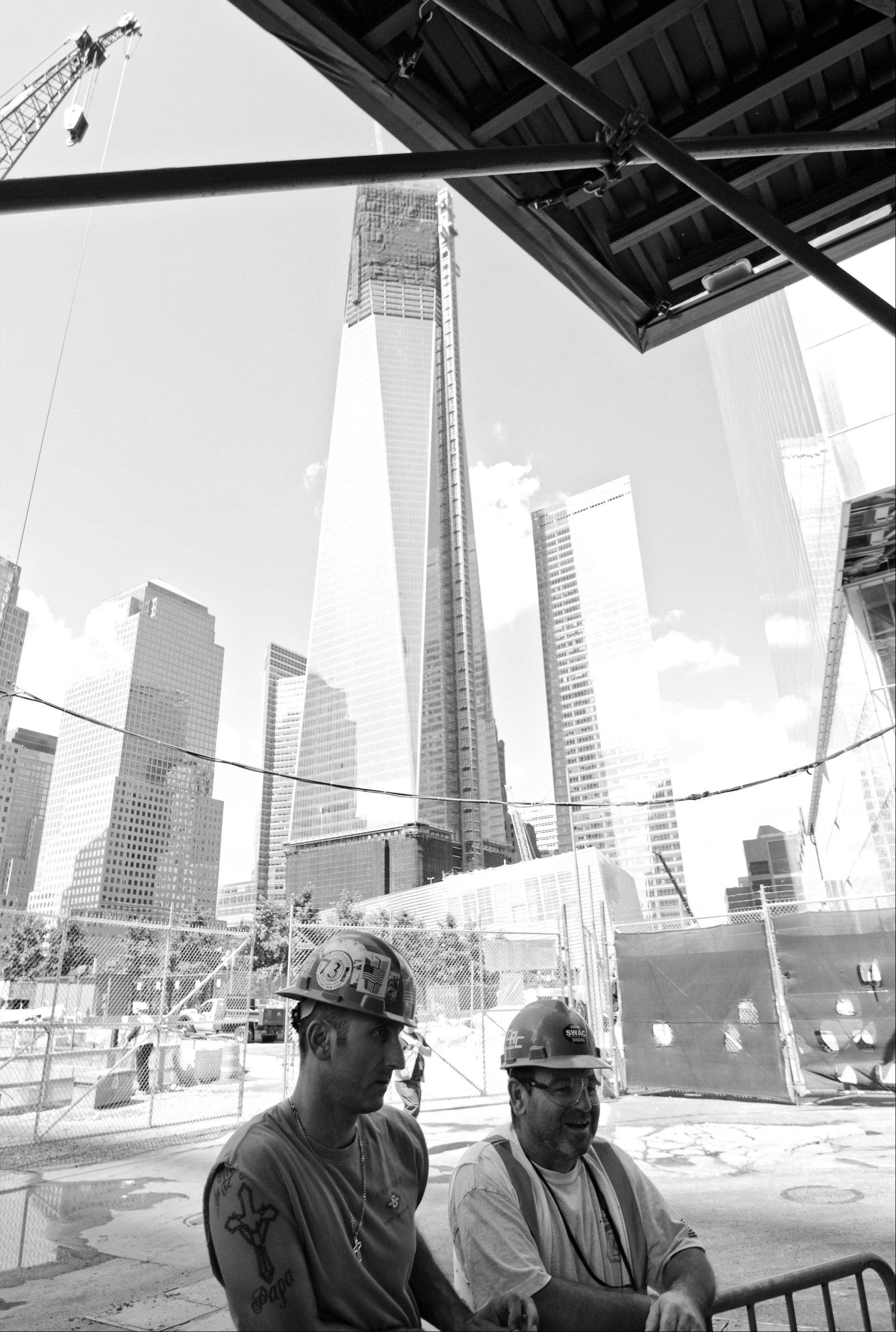 Two men at work building the new World Trade buildings in Manhattan, take a break near visitors of the September 11, 2001 memorials bearby. Eleven years after the fall of the twin towers, the real story is not necessarily the rebuilding of the physical towers, but the ability for Americans to continue their lives and appreciate New York City as the rich cultural center that it is.