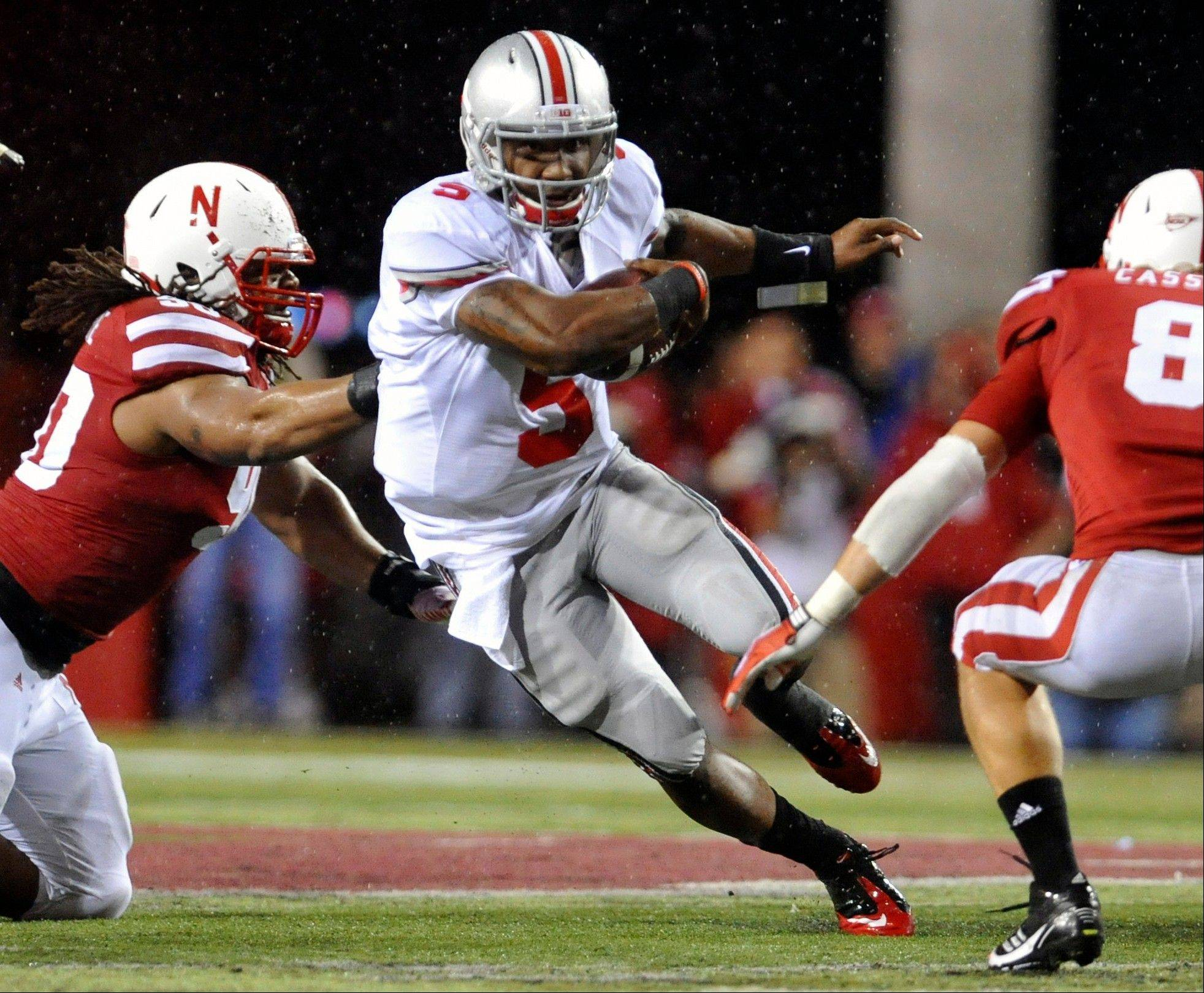 Ohio State quarterback Braxton Miller runs past Nebraska's Terrence Moore, left, and Austin Cassidy when the two teams met in 2011.