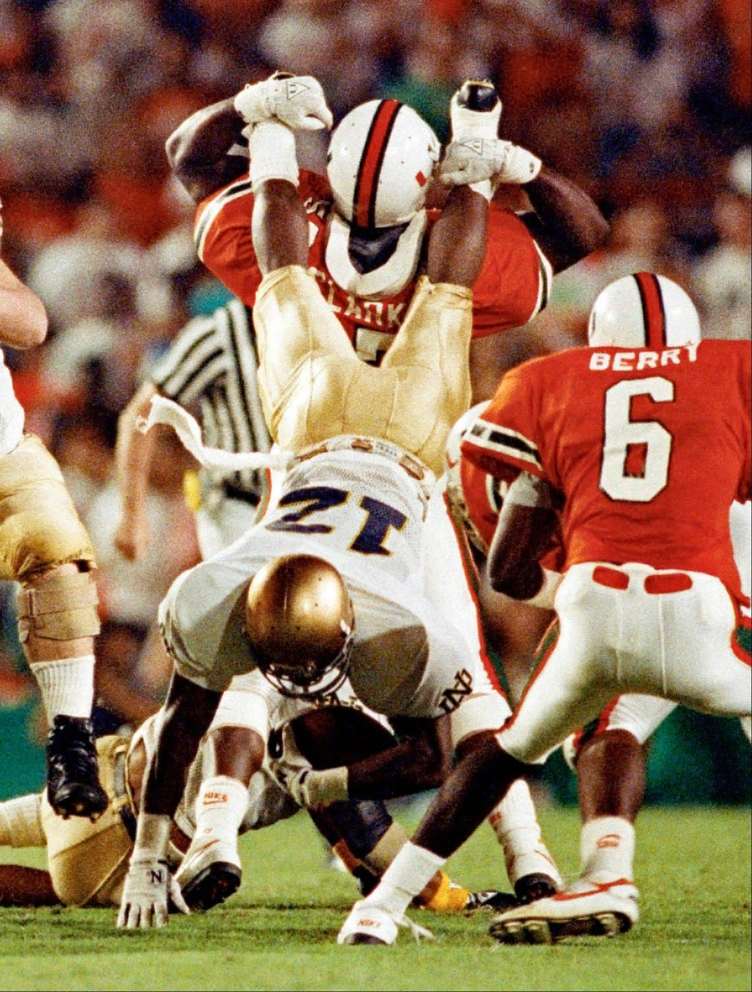 Notre Dame tailback Ricky Watters gets upended by Miami linebacker Bernard Clark during the first half at the Orange Bowl at Miami. For the first time in nearly a quarter-century, the Fighting Irish and Hurricanes are meeting in a regular-season game. The rivalry will be renewed Saturday at Soldier Field.