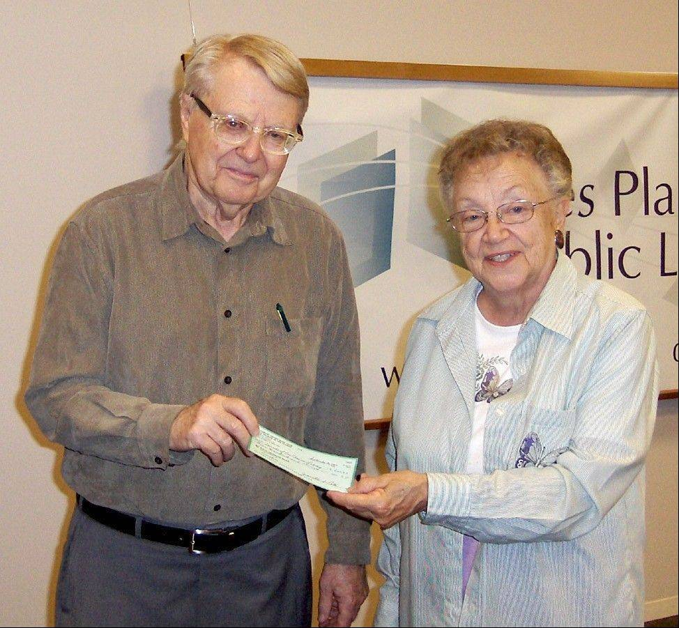 Sue D'Hondt from the Literary Review Book Club presents a $500 donation to Wally Meyer, president of the Friends of the Library, to be used to fund a special purchase for the library.