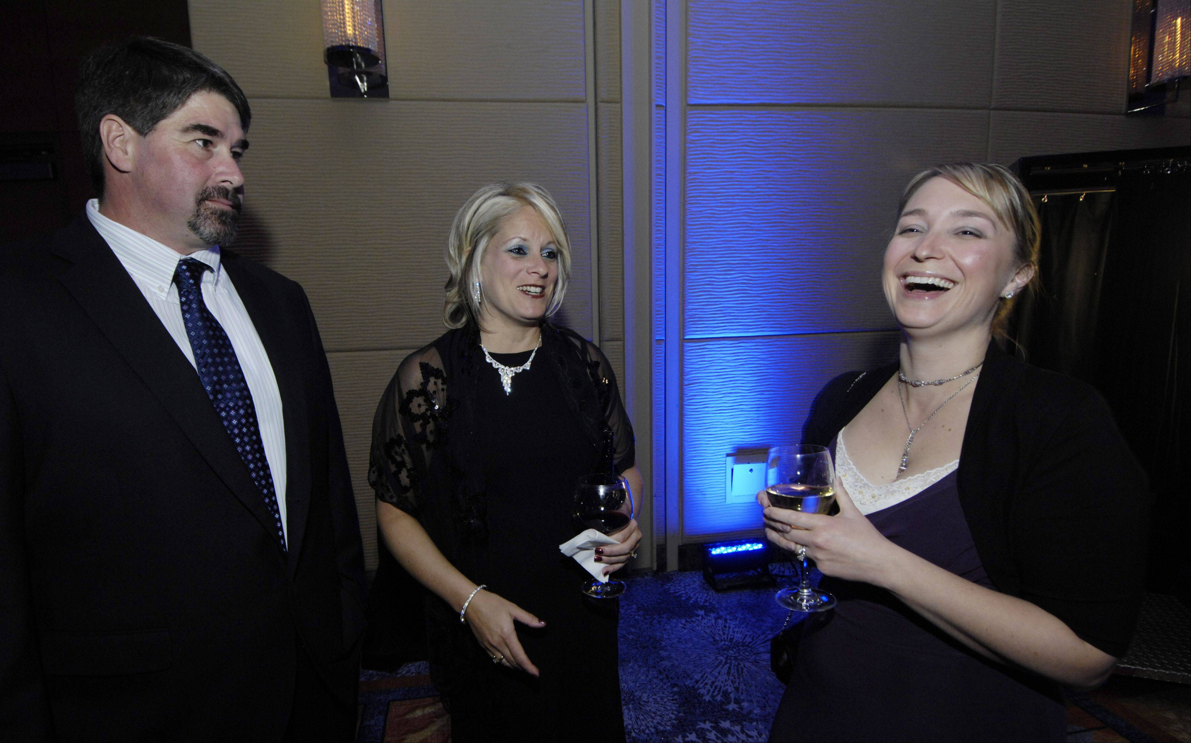 JOE LEWNARD/jlewnard@dailyherald.com Left to right, Greg and Chris Vanhauter of Elk Grove Village and Lisa Augustine chat during the Schaumburg Business Association gala and awards Saturday at the Renaissance Convention Center Hotel.
