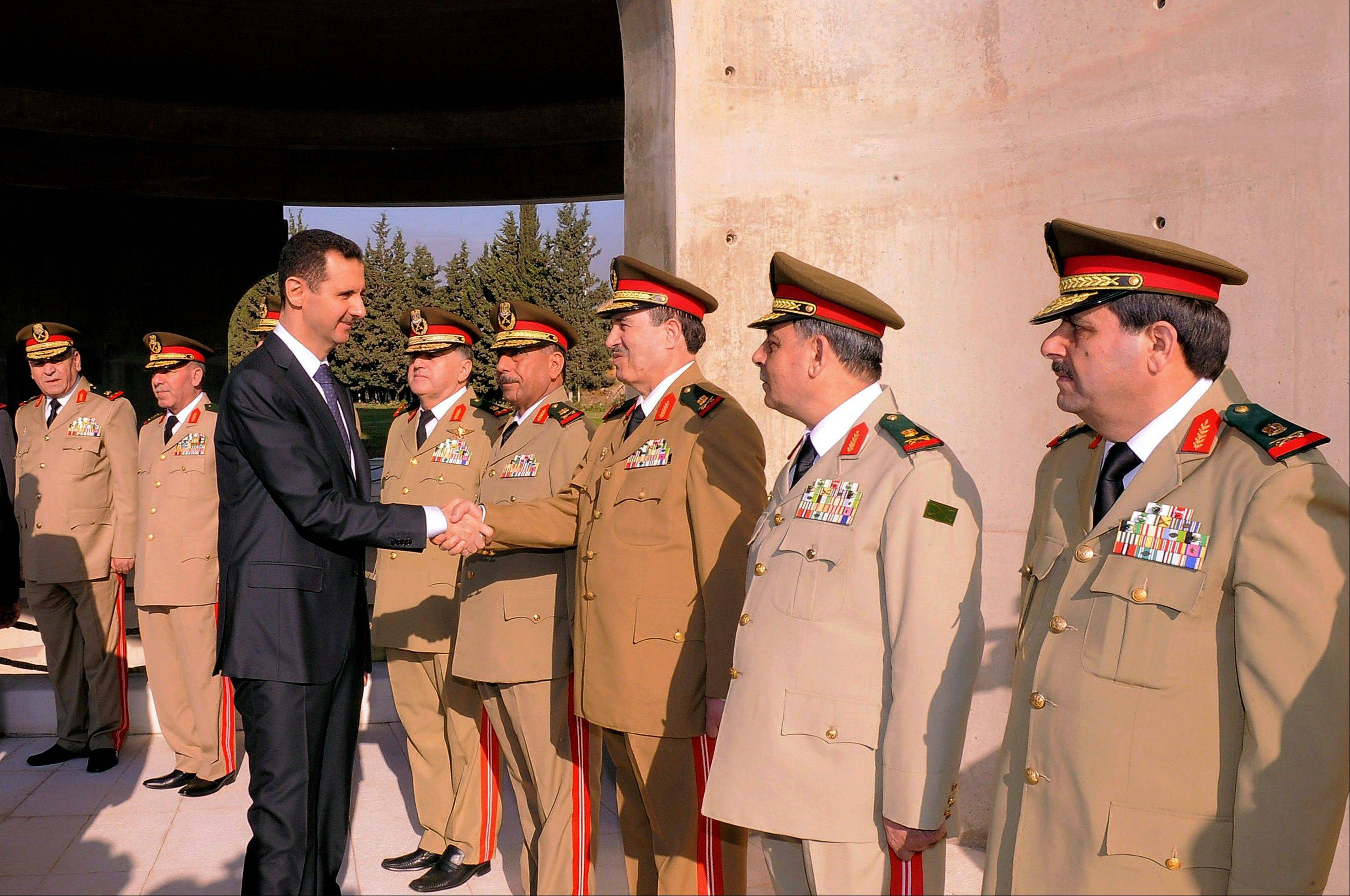 Syrian President Bashar Assad greets military officers Saturday in a ceremony marking the anniversary of the 1973 Arab-Israeli war in Damascus, Syria.